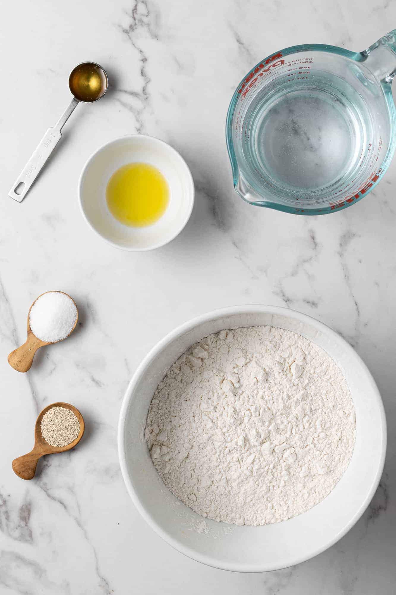Overhead view of ingredients needed to make dutch oven bread: flour, oil, yeast, water, salt, honey.