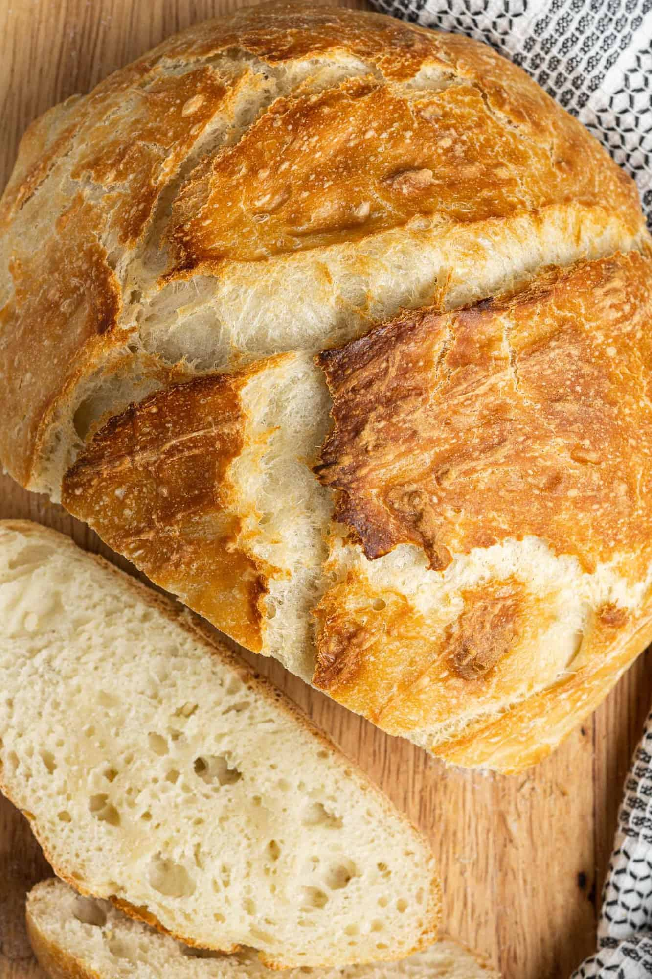 Overhead view of round loaf of bread with one or two slices removed.
