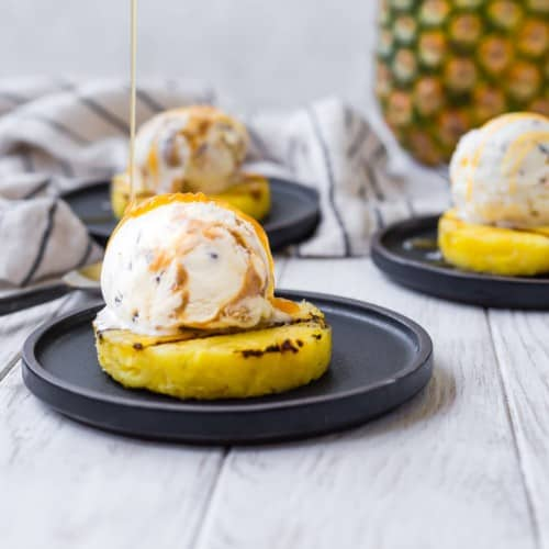 Grilled pineapple on a black plate, topped with ice cream, being drizzled with caramel.