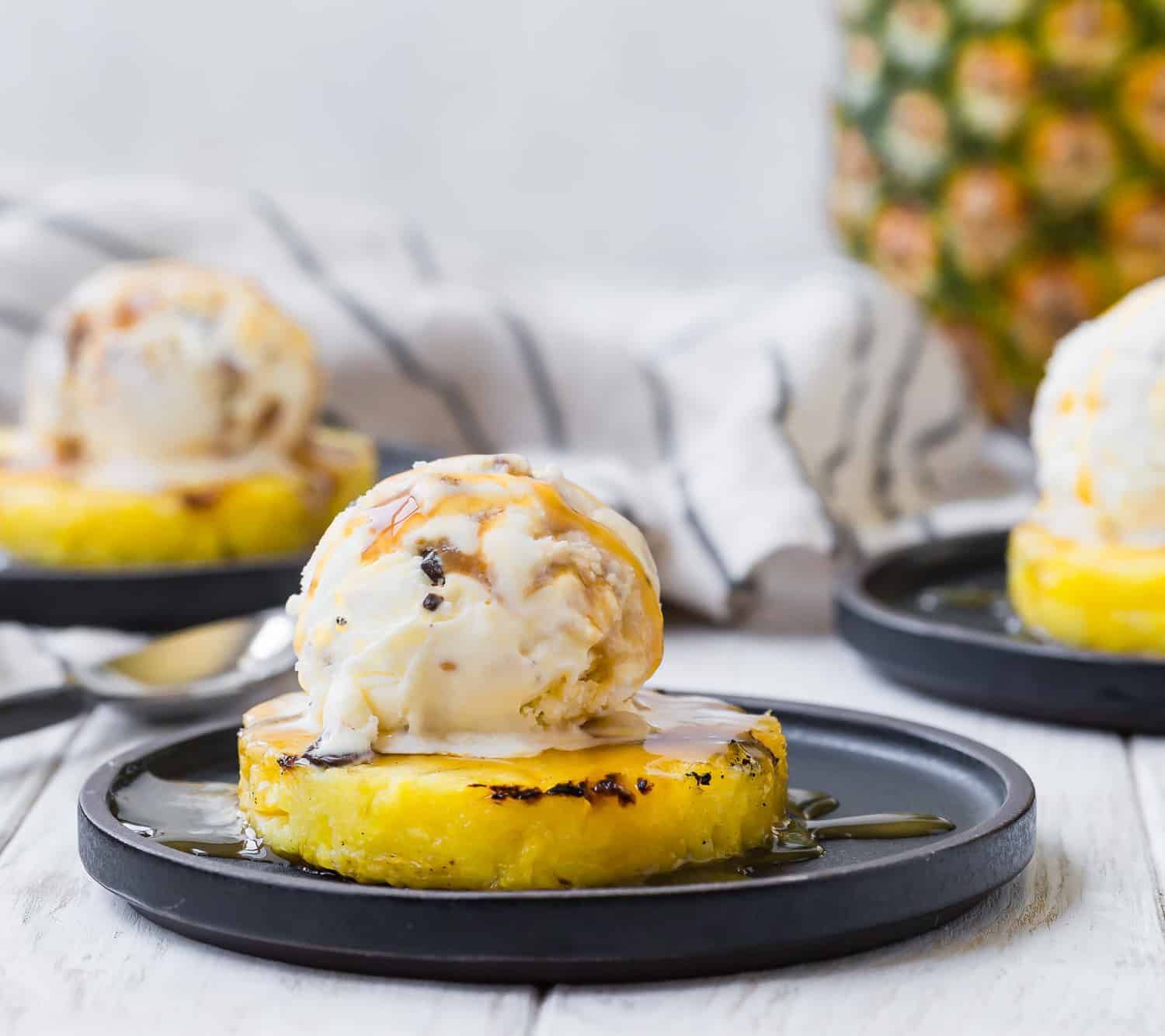 Grilled pineapple slice topped with ice cream. Additional servings in background.