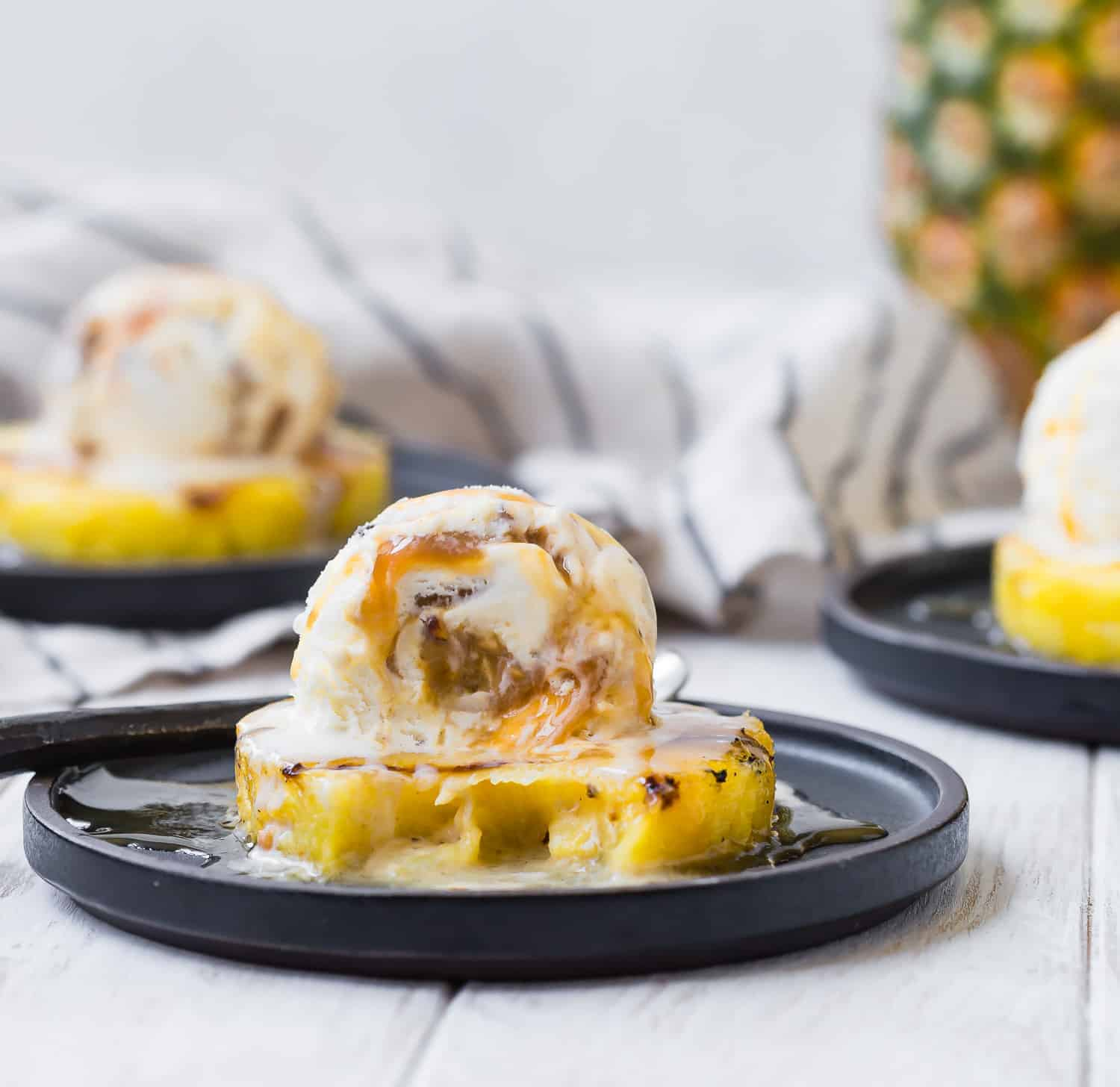 Pineapple and ice cream with a bite out of it to show caramel in ice cream.