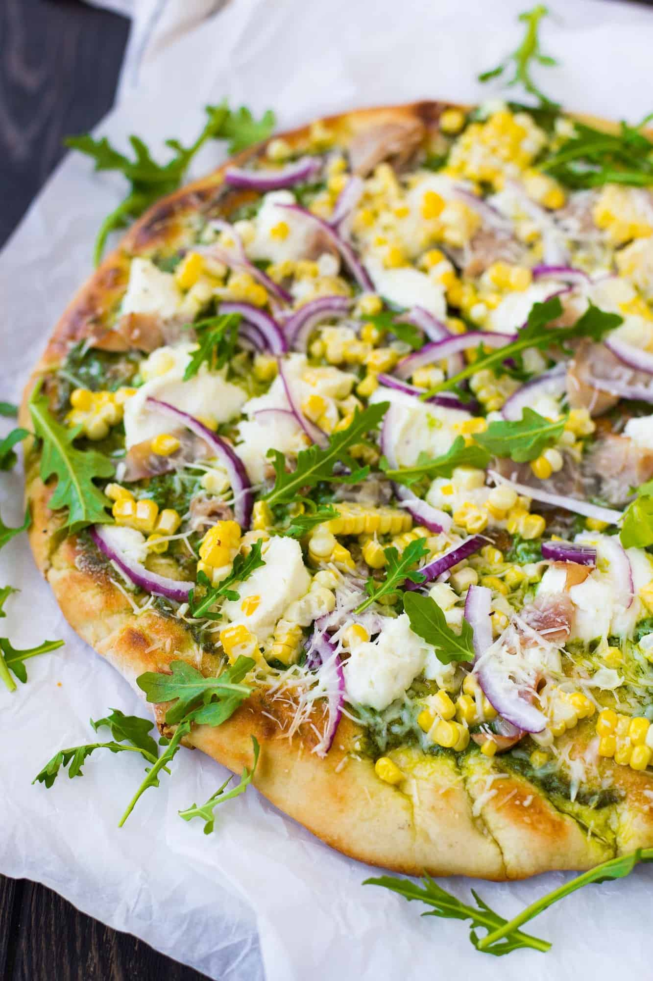 Grilled pizza on a piece of parchment, topped with ricotta cheese, arugula, and more.