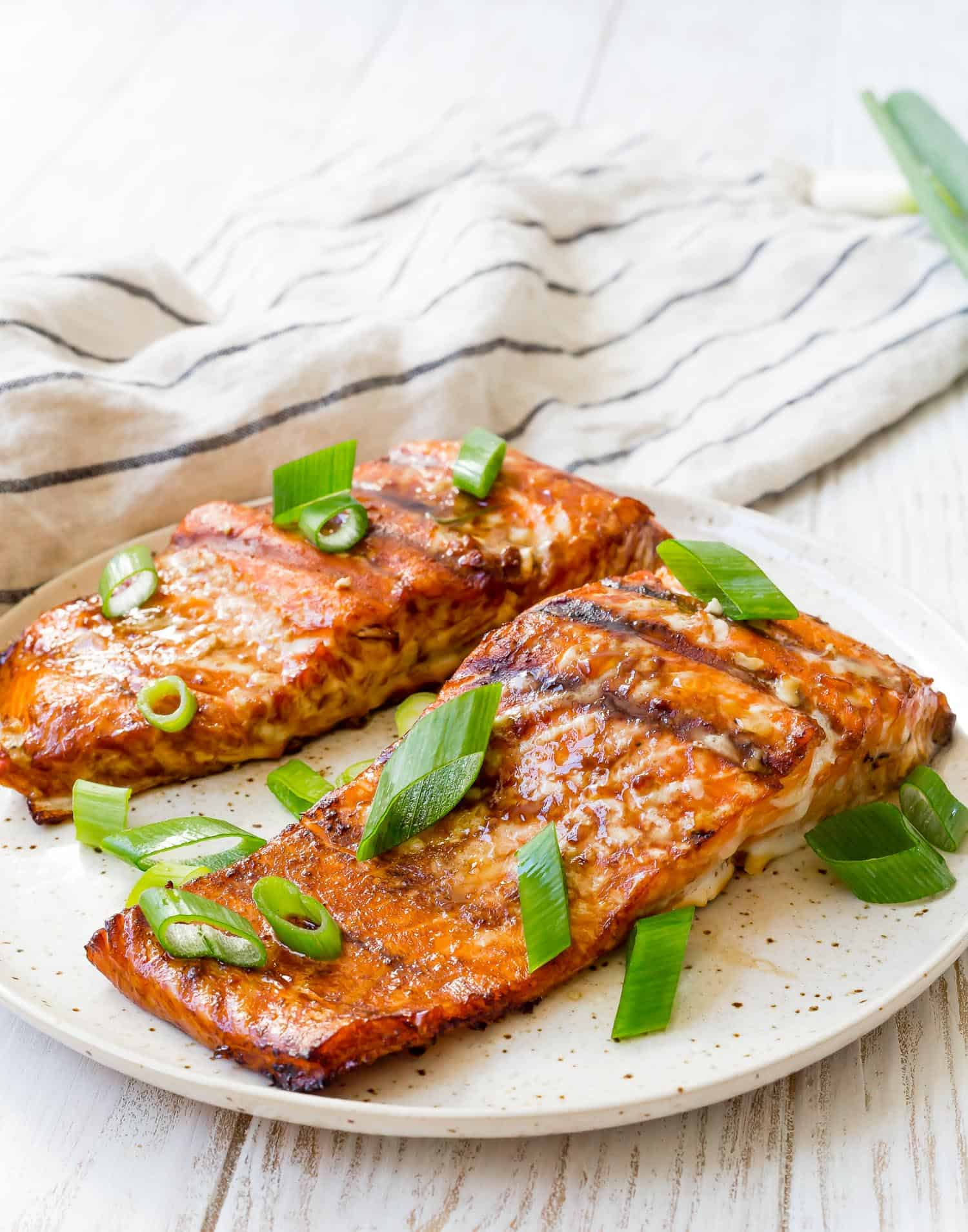 Two fillets of grilled salmon topped with green onion.