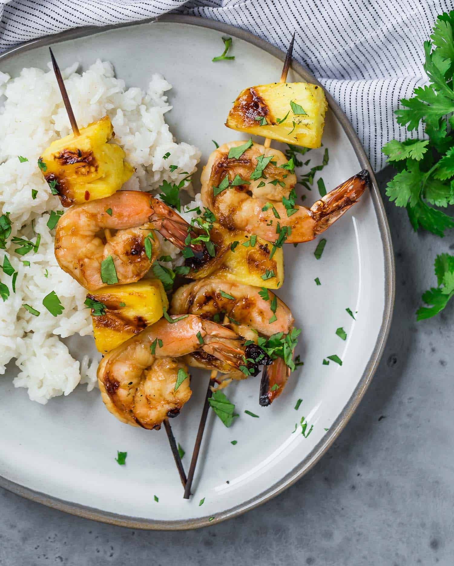 Overhead view of two grilled kabobs on a plate, with shrimp and fresh pineapple. They are served with white rice and sprinkled with fresh cilantro.