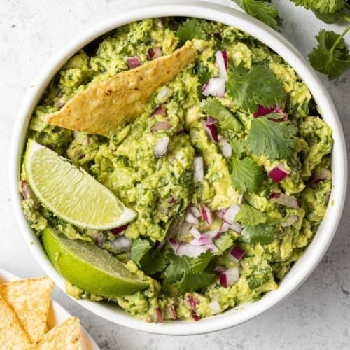 Round white bowl filled with guacamole, one chip dipped in.