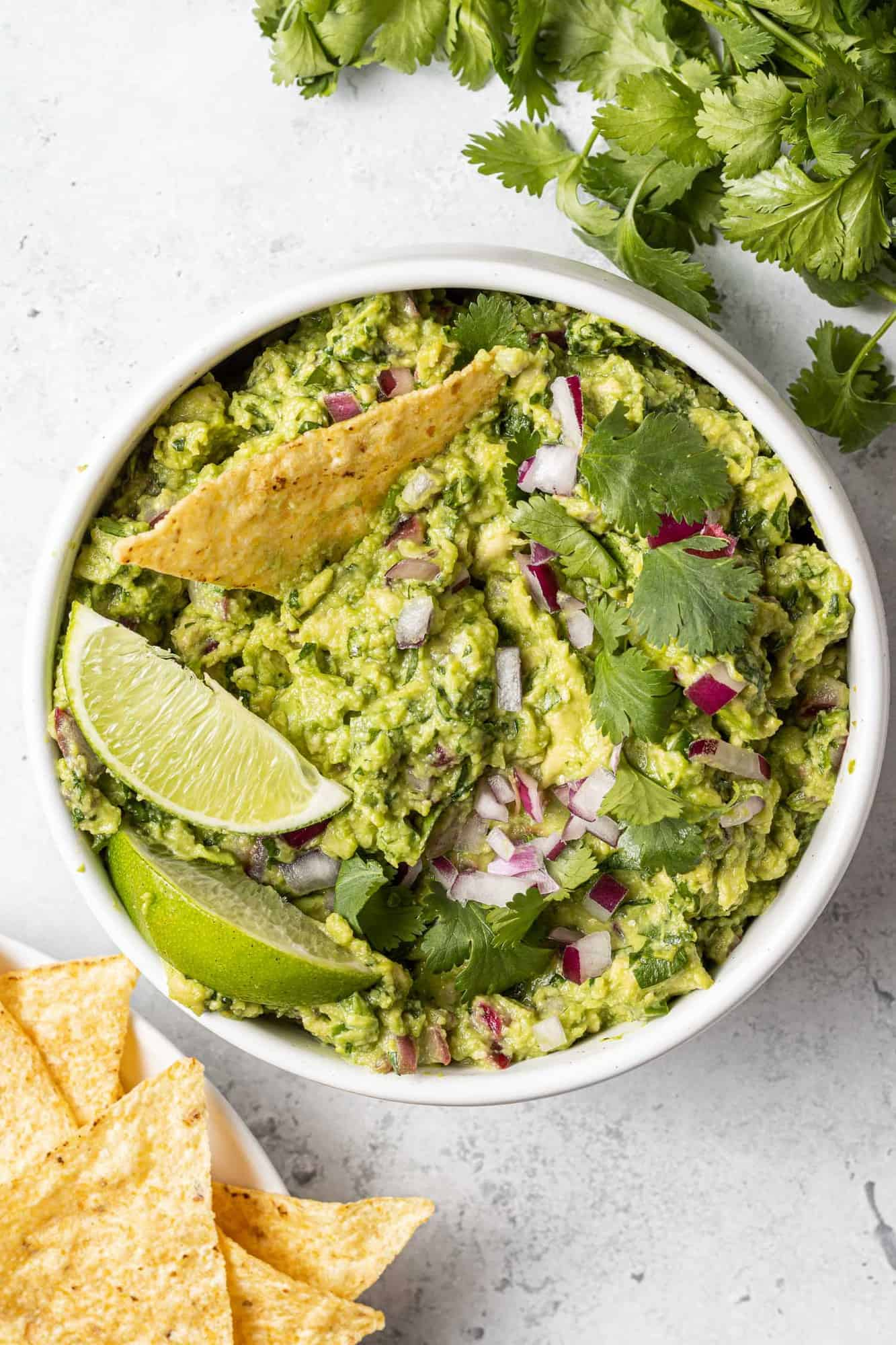 Overhead view of a white bowl of guacamole with a chip dipped in and lime wedges on top.