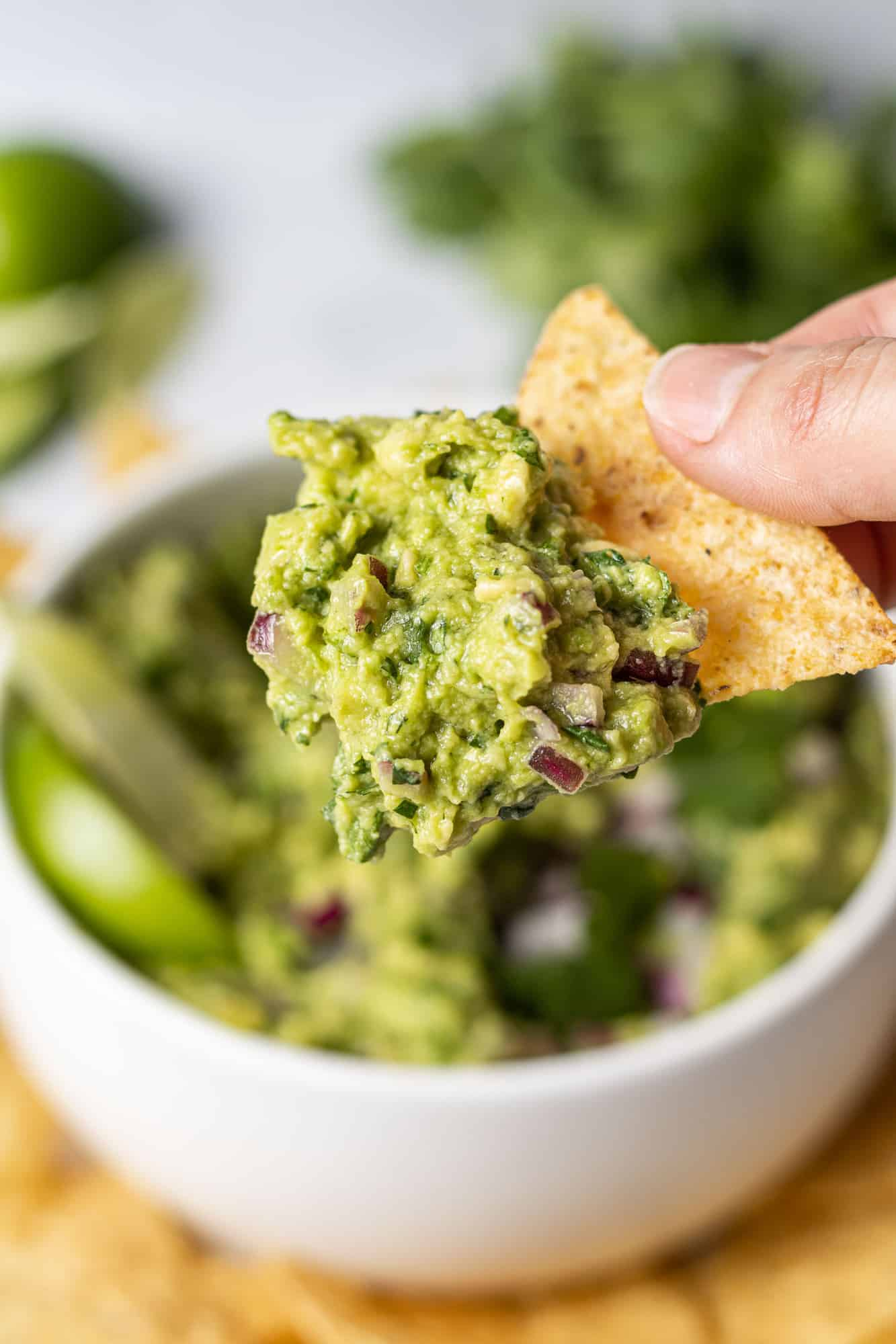 Guacamole on a chip held in a hand.