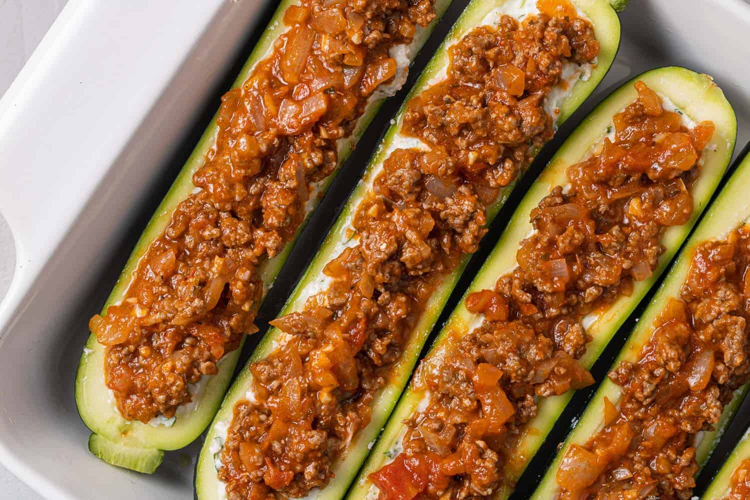 Zucchini boats topped with meat sauce.