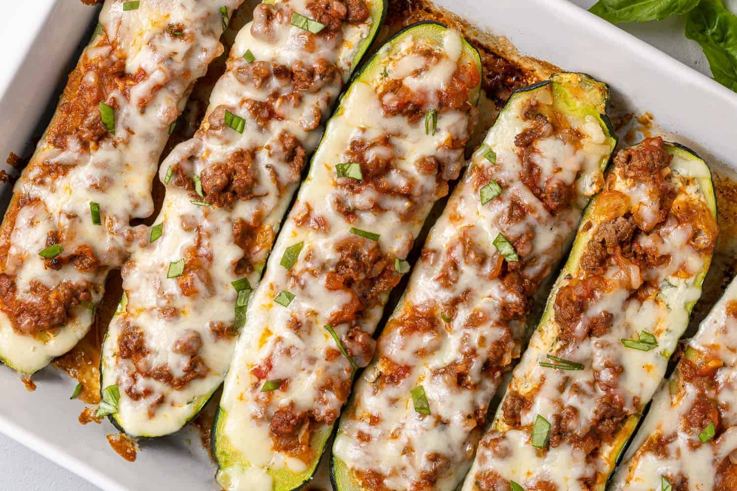 Stuffed zucchini topped with meat sauce and cheese.
