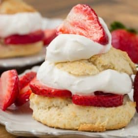 Layered strawberry shortcake on a white plate.