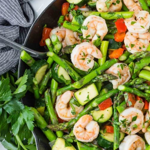 Overhead view of shrimp and vegetables in a white skillet.