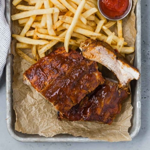 Barbecued ribs on a tray with fries and ketchup.