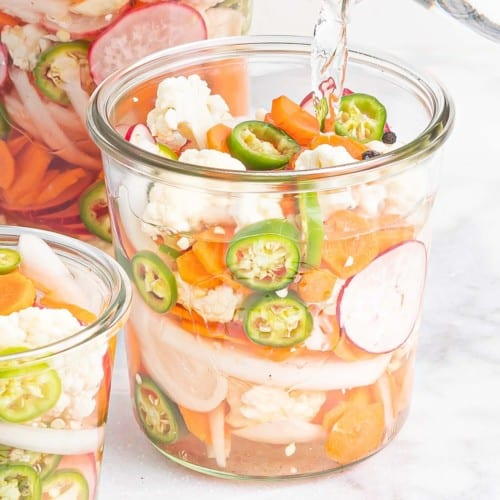 Vegetables in a jar with liquid being poured into it.