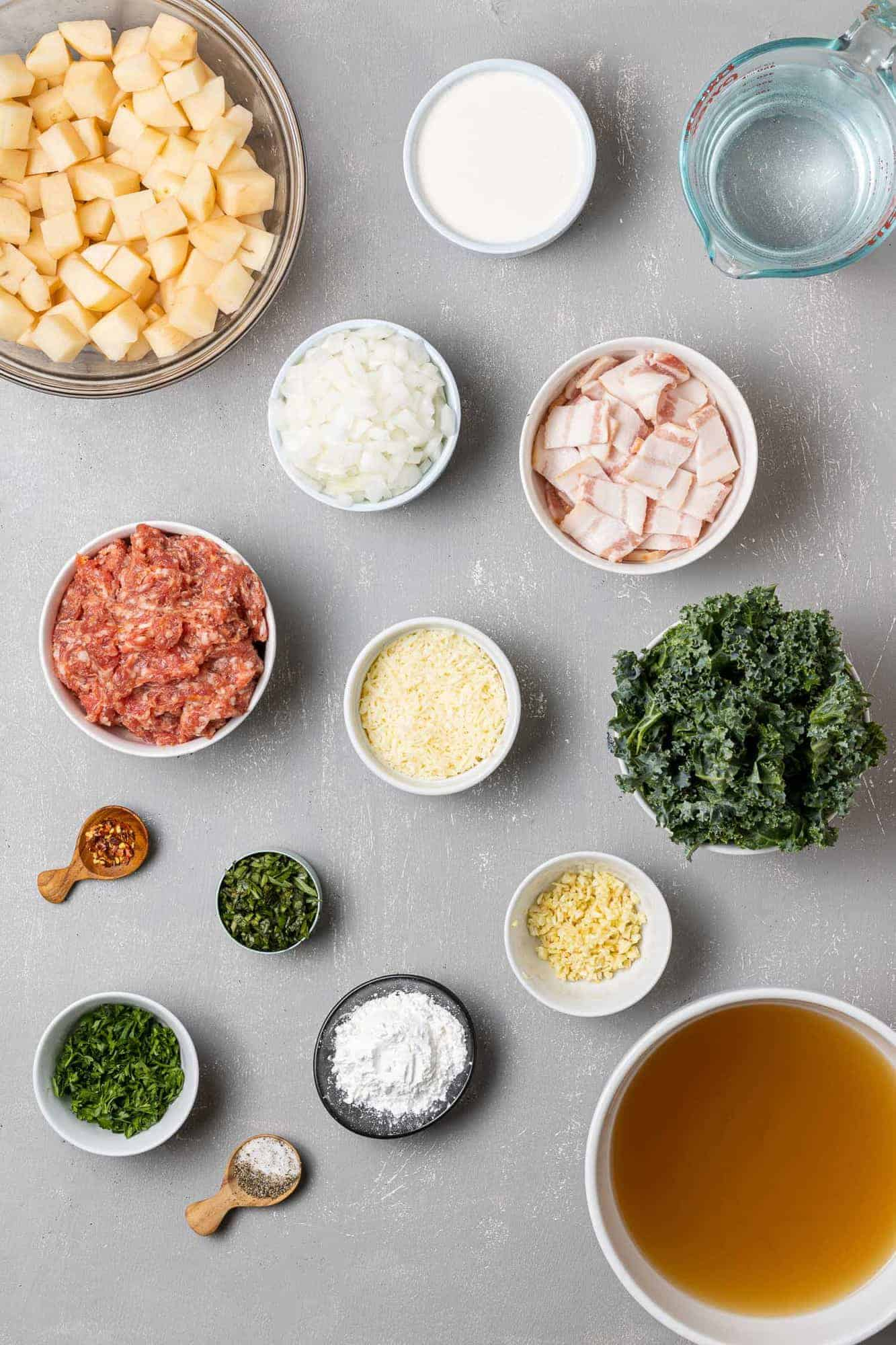 Overhead view of ingredients needed for recipe: sausage, potatoes, kale, and more.