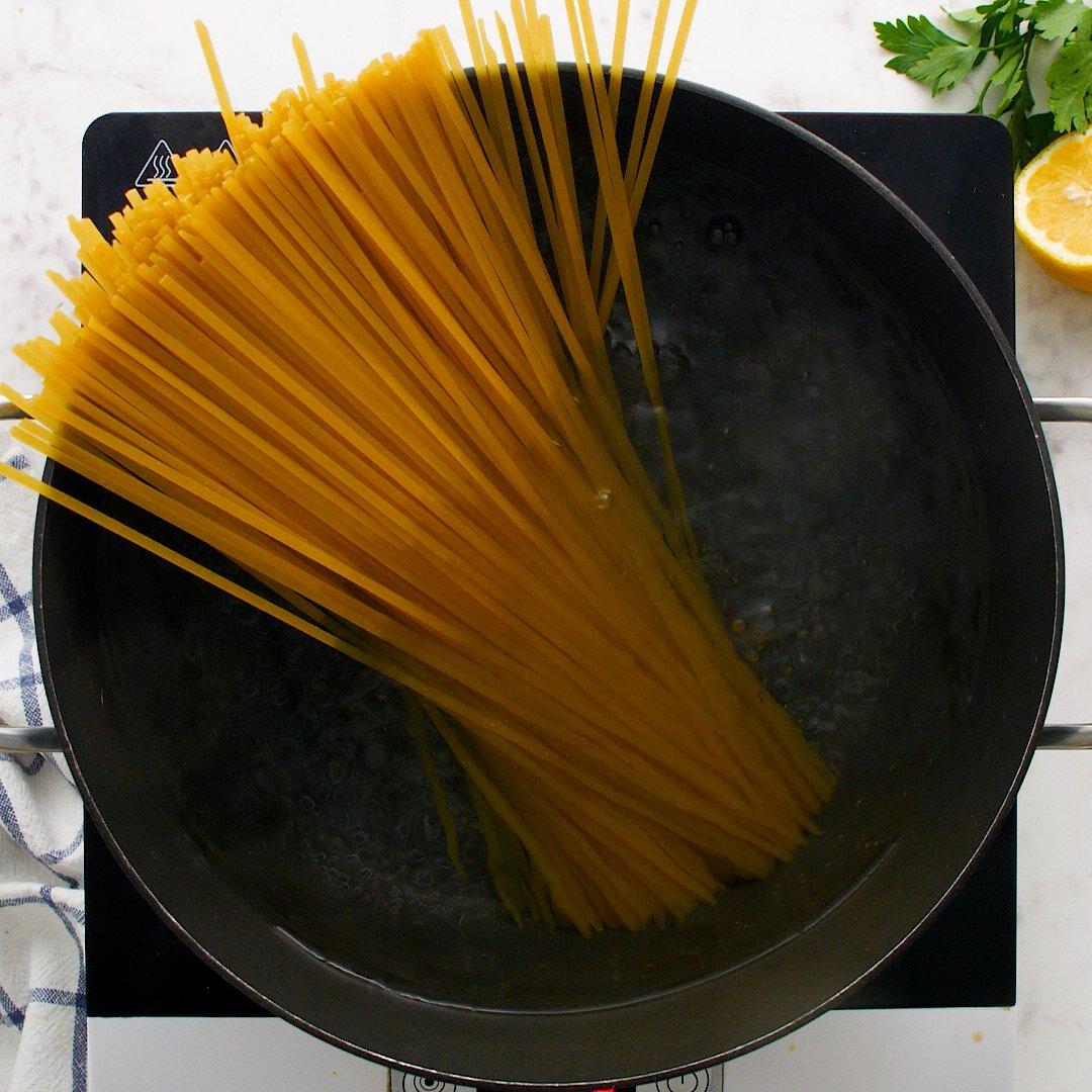 Pasta in a large black pot.
