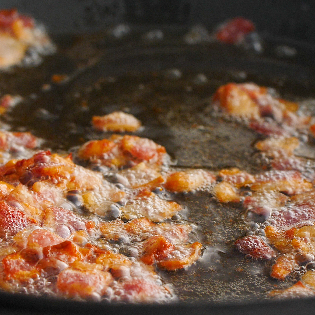 Pancetta cooking in a black pan.