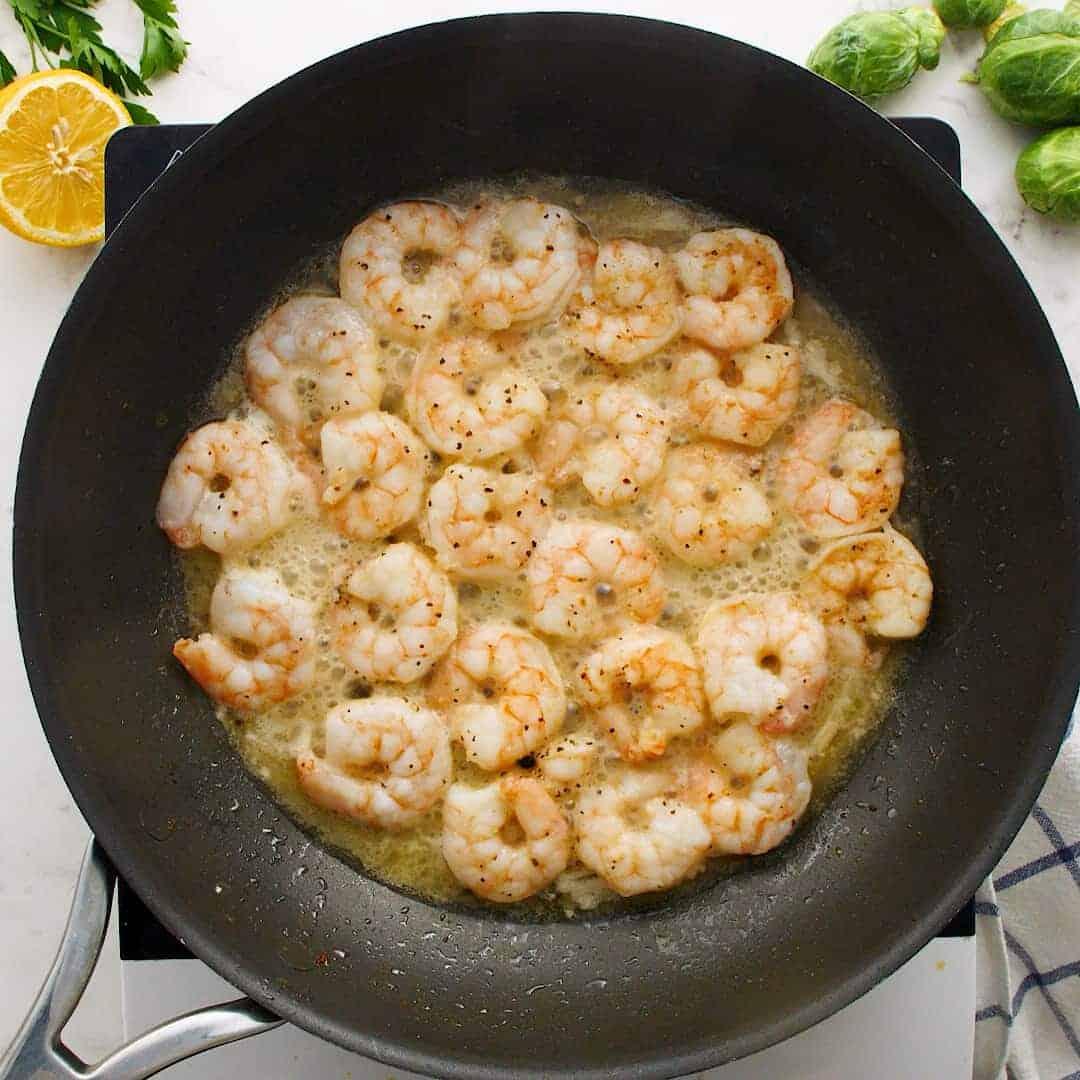 Cooked shrimp in a black skillet.