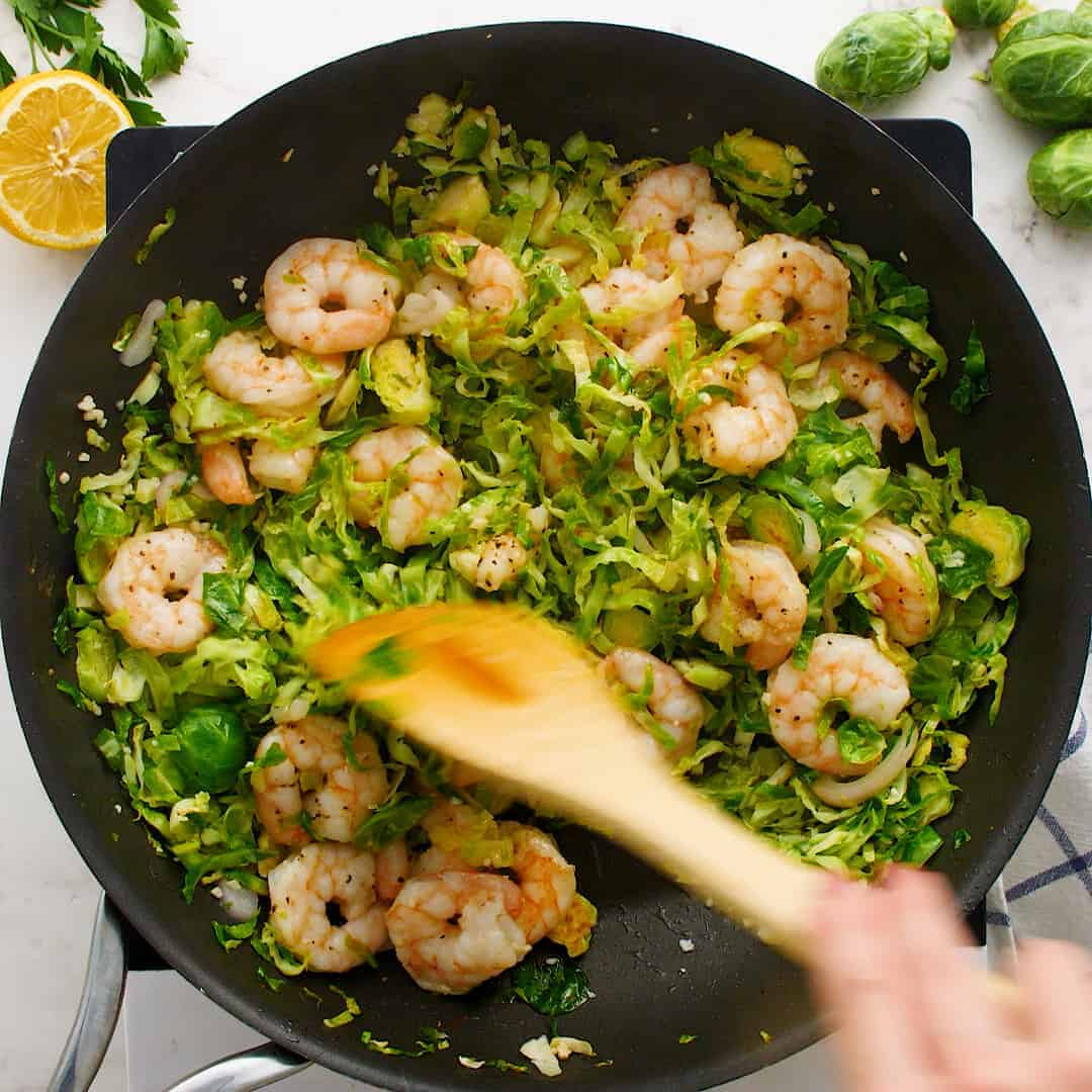 Shrimp and brussels sprouts in a skillet.