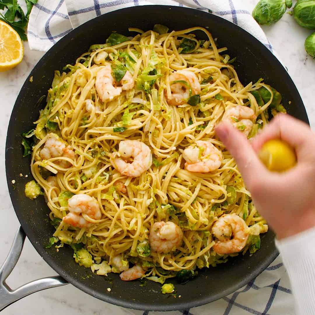 Lemon being squeezed over pasta with Brussels sprouts.
