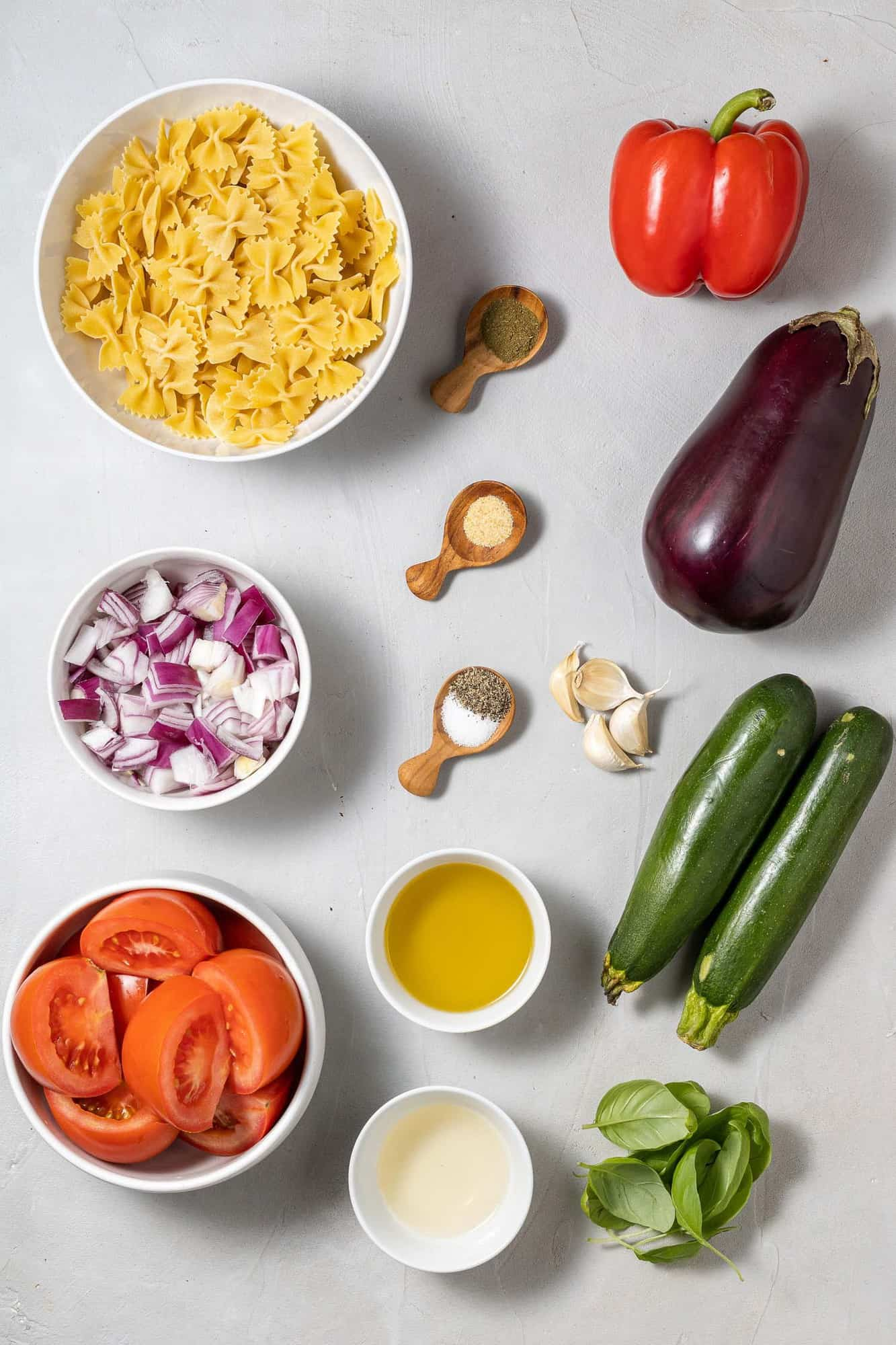 Fresh vegetables, cooked pasta, and dressing ingredients on a gray background.