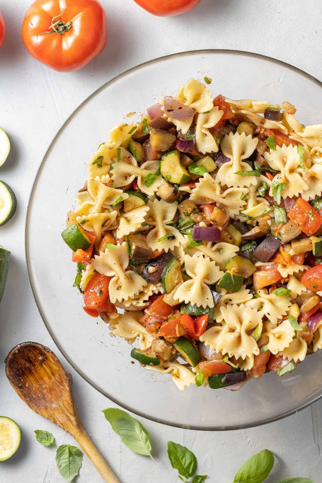 Pasta salad in a clear glass mixing bowl.