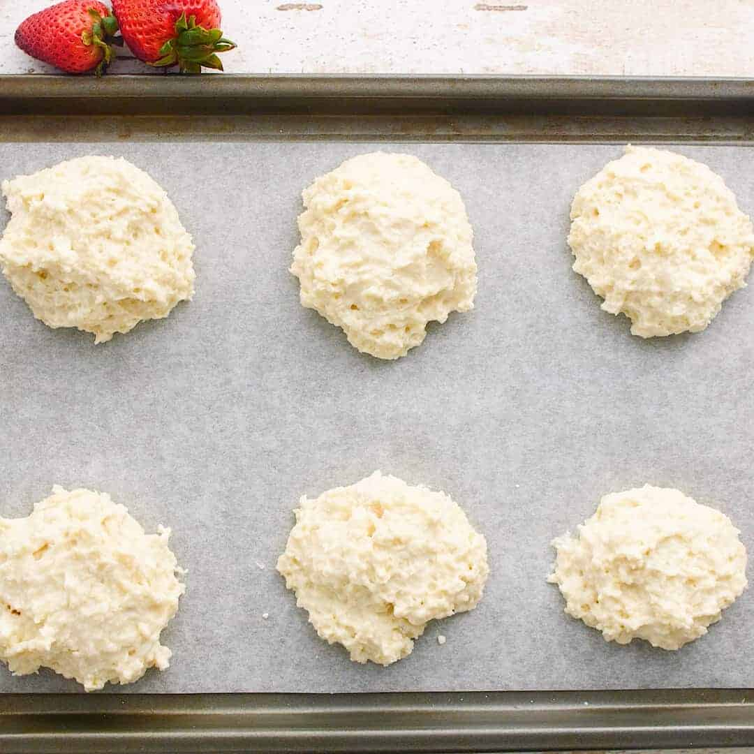 Unbaked shortcakes on a tray.