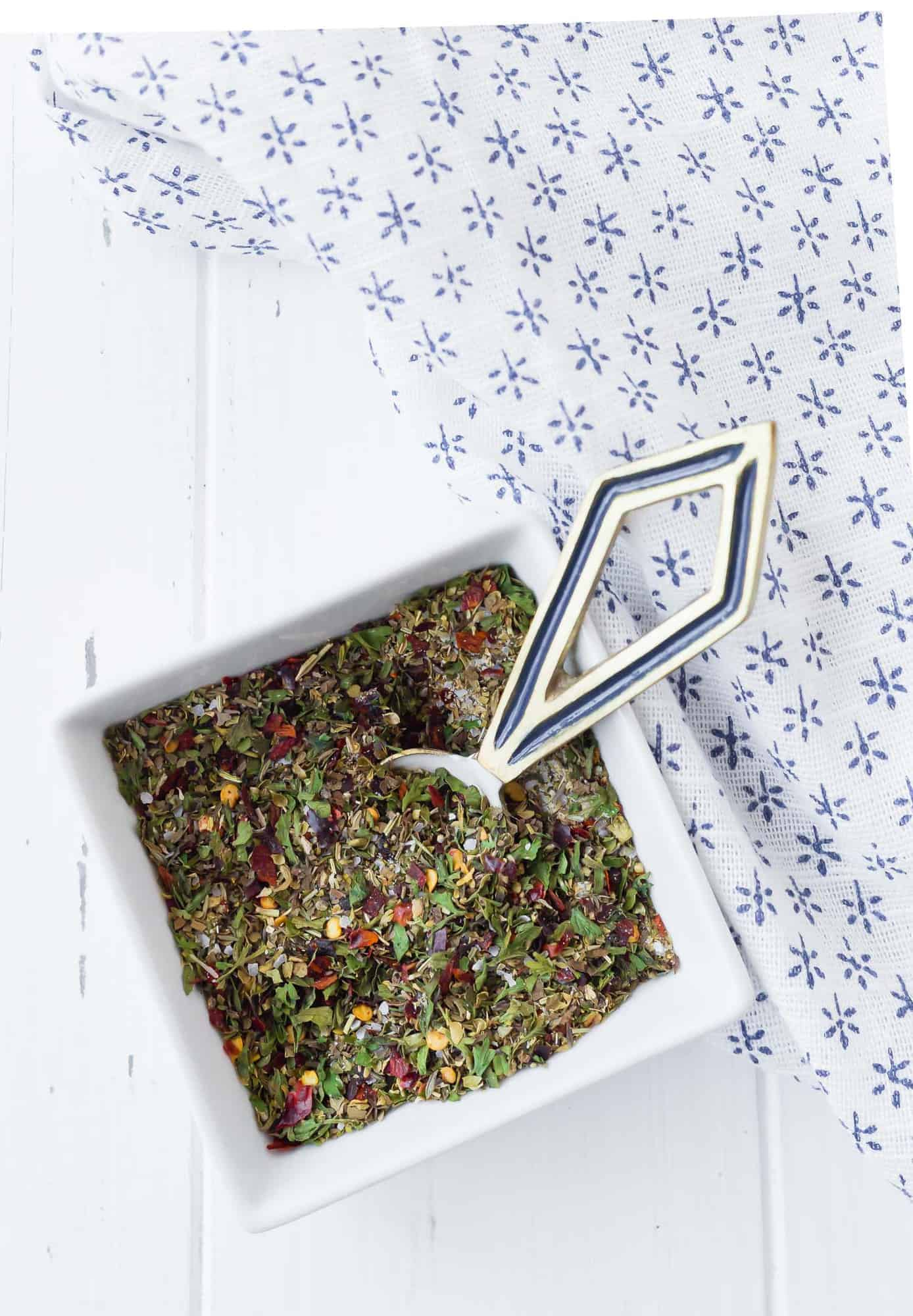Dried herbs and spices in a small square white bowl with a decorative measuring spoon.