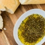 Overhead view of bread dipping oil and bread on a wooden surface.