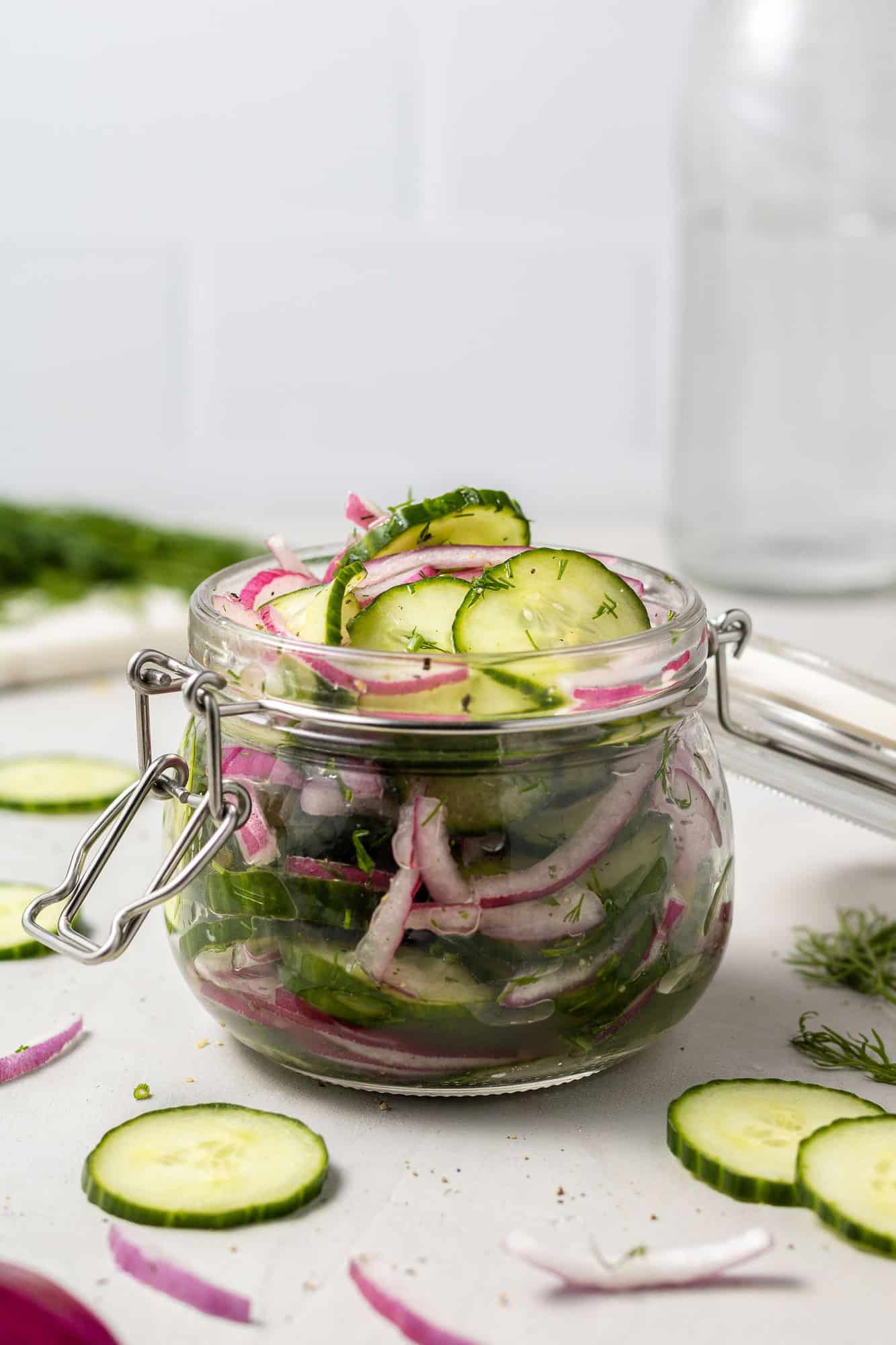 Jar filled with sliced cucumbers and onions in a brine.