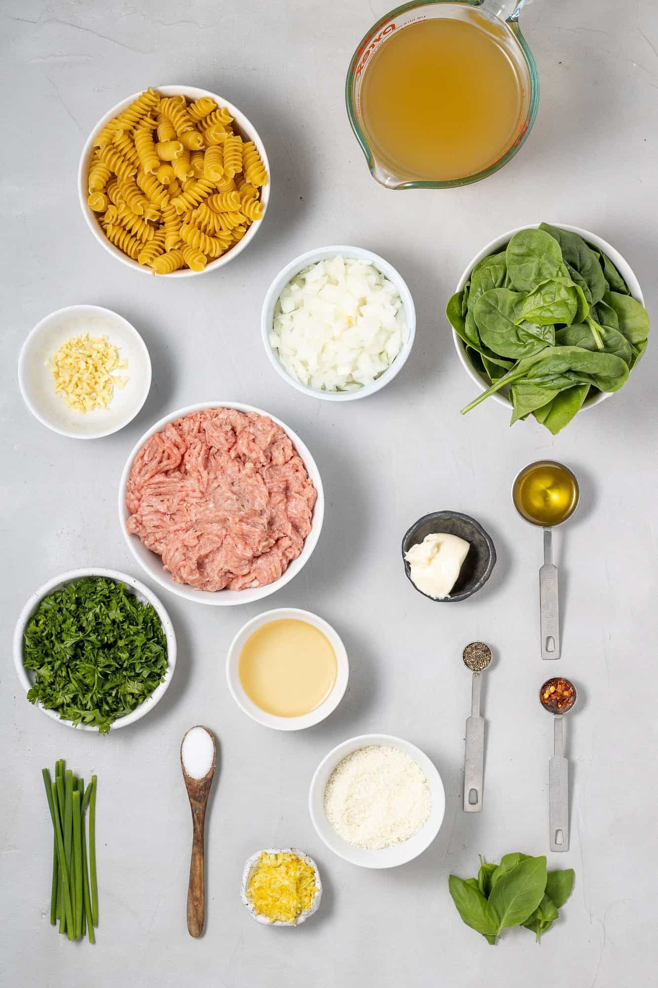 Overhead view of ingredients needed for recipe, including ground chicken, spinach, and lemon.