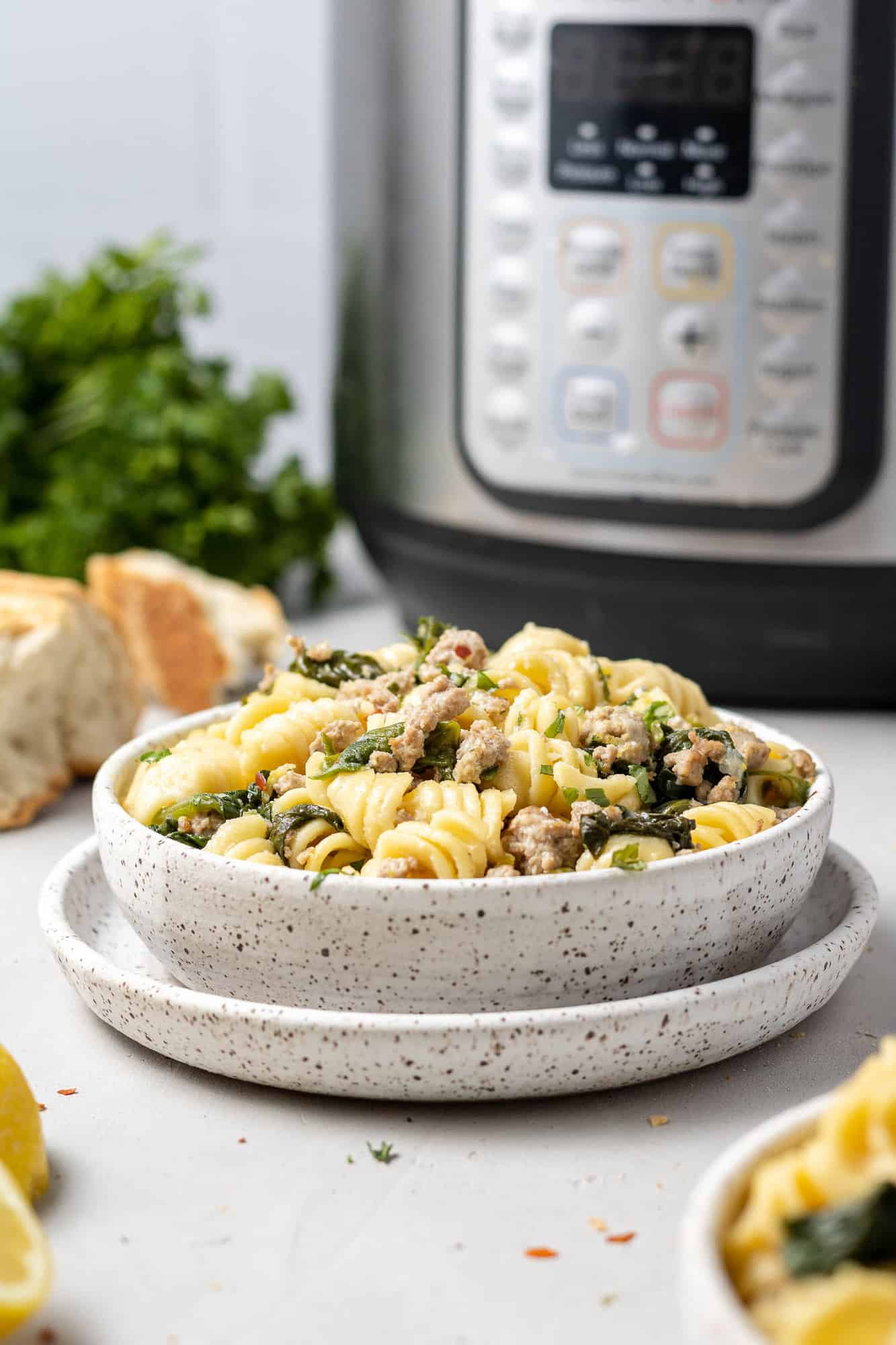 Bowl of instant pot lemon pasta with an instant pot in background.
