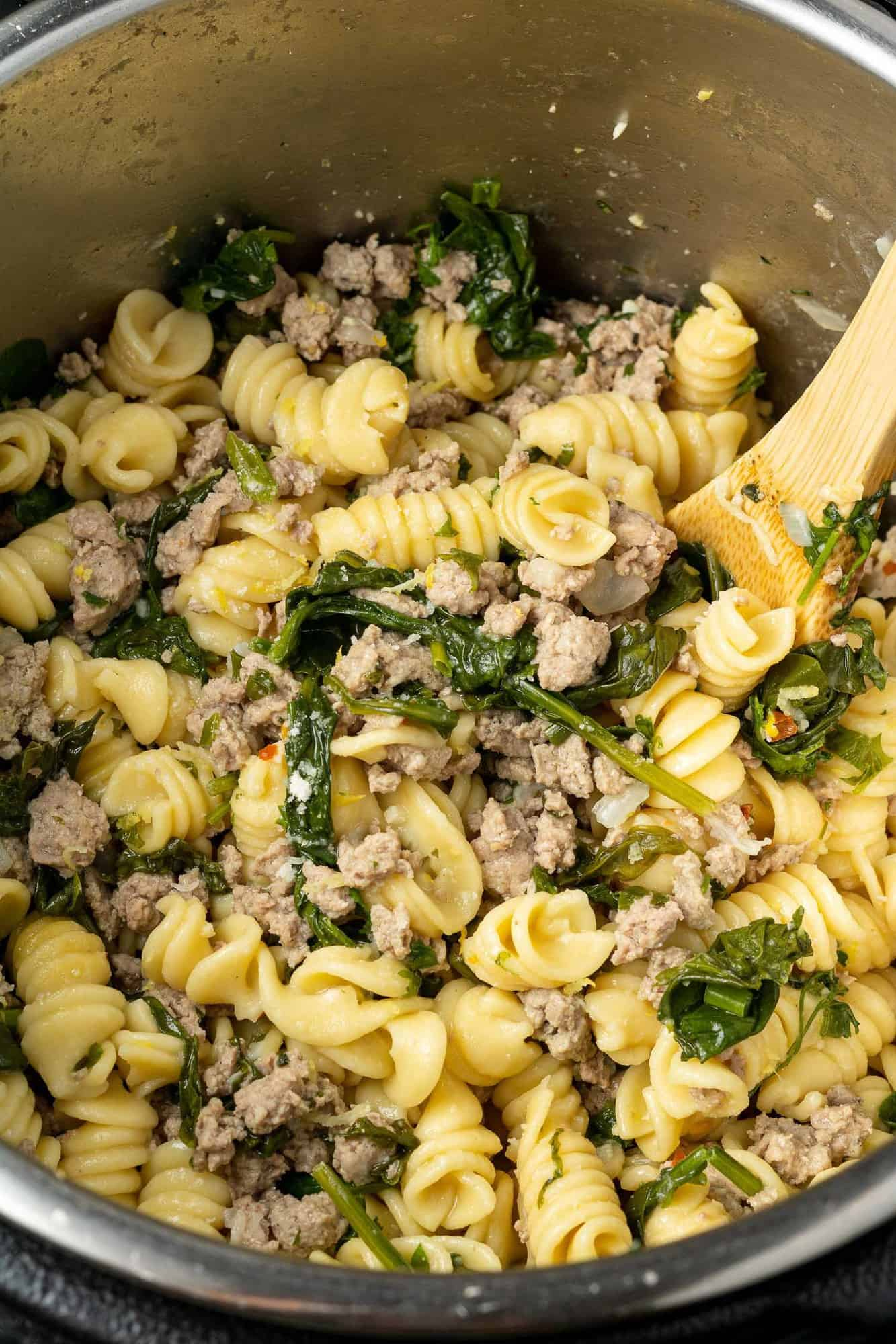 Instant pot filled with pasta, spinach, ground chicken, and a wooden spoon.