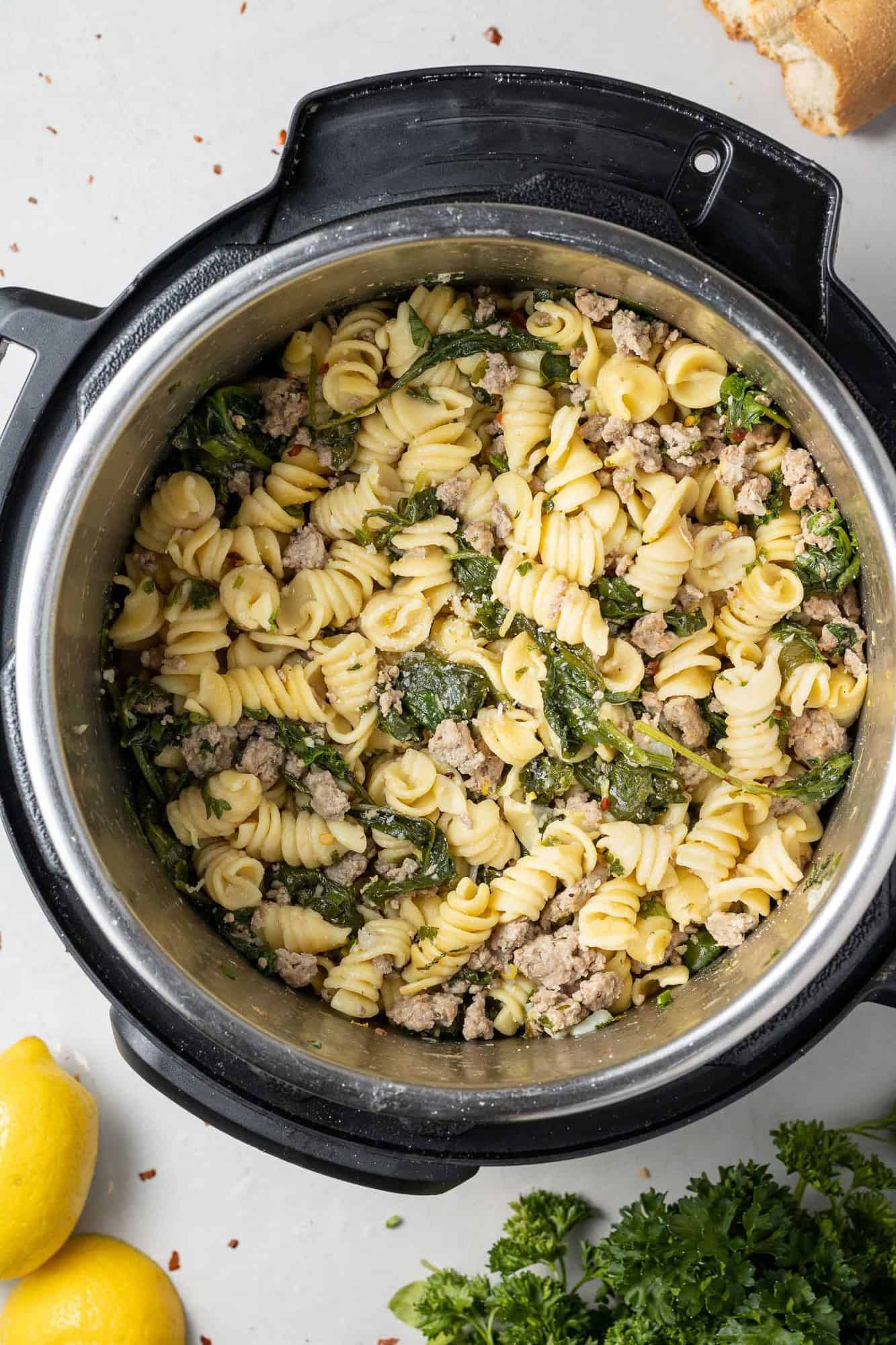 Overhead view of instant pot with pasta, spinach, and ground chicken.