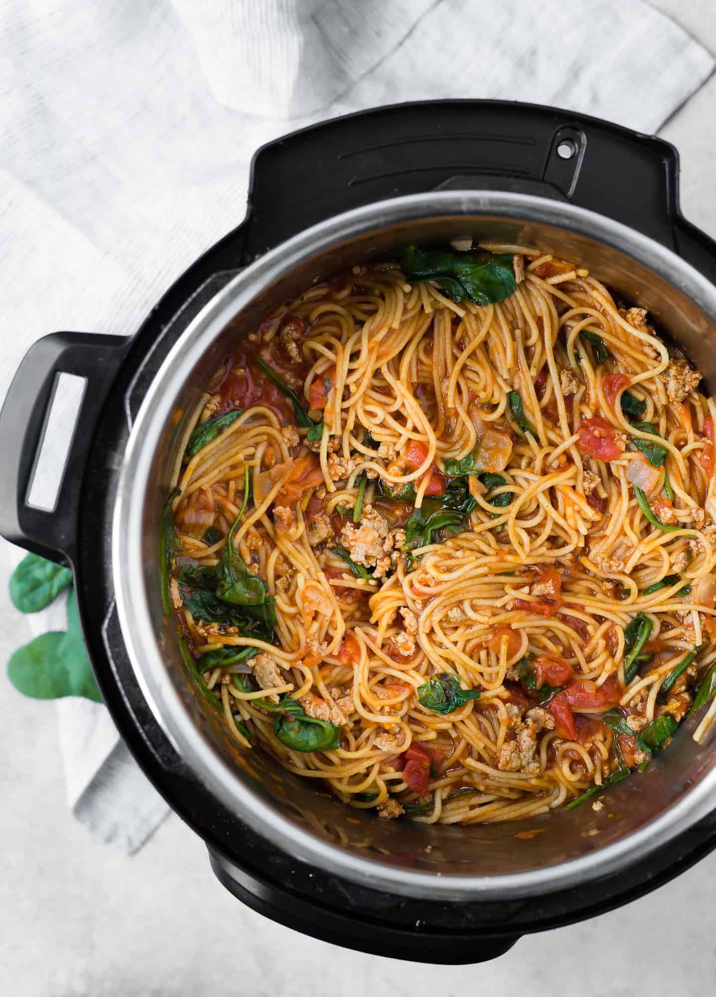Overhead view of spaghetti in an instant pot, with a meat sauce and spinach.