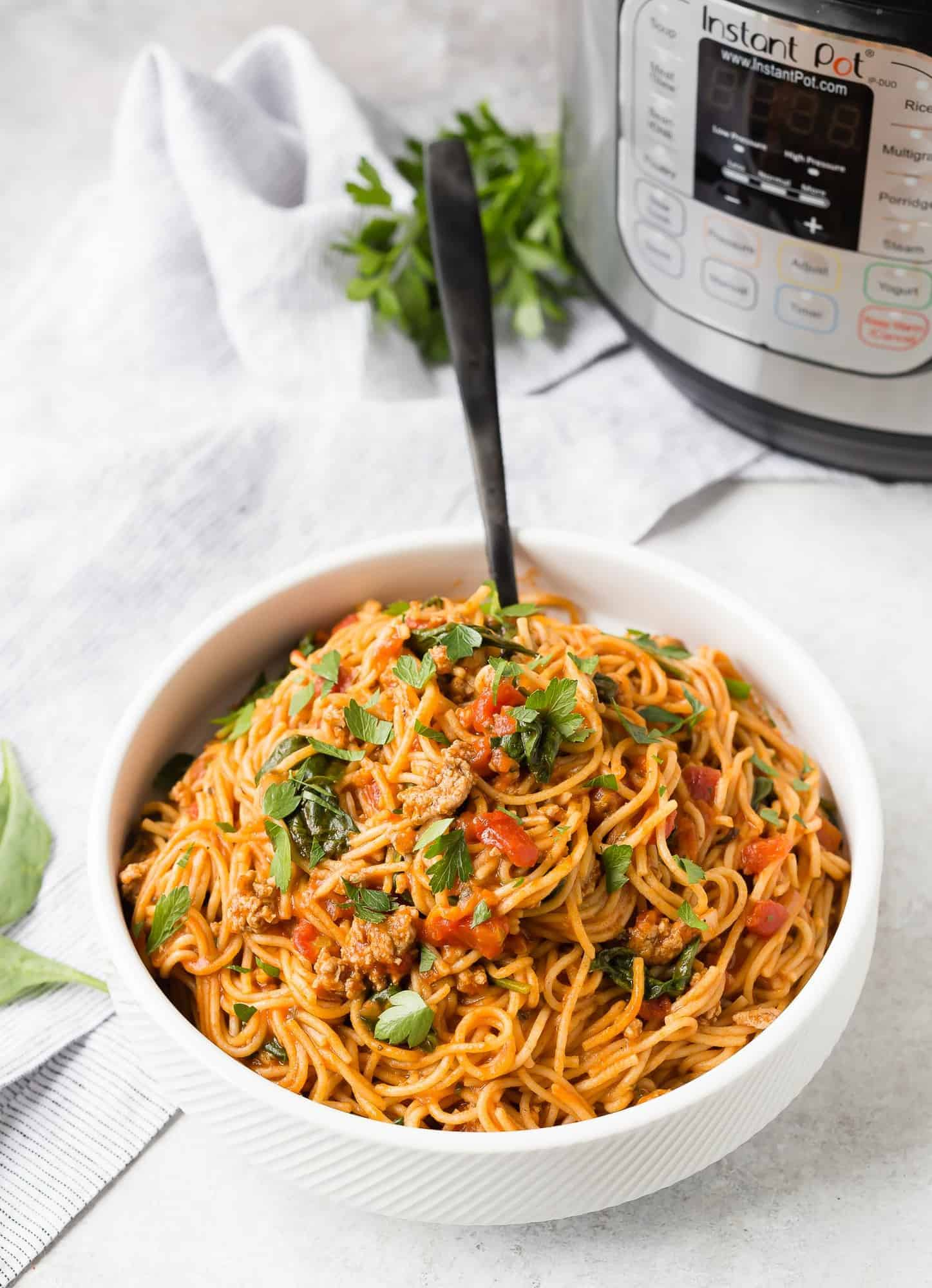 A large white bowl filled with spaghetti in tomato sauce, a pressure cooker and fresh parsley in the background of the image.