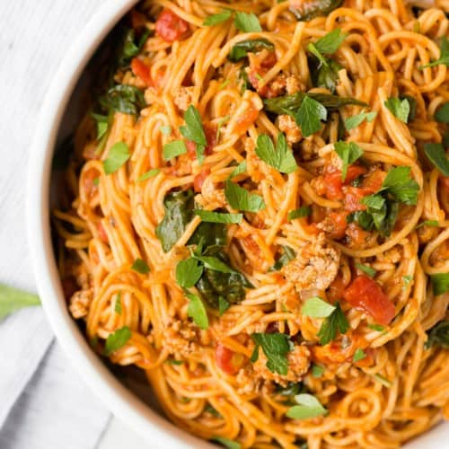 Overhead view of spaghetti and meat sauce in a white bowl, sprinkled with parsley.