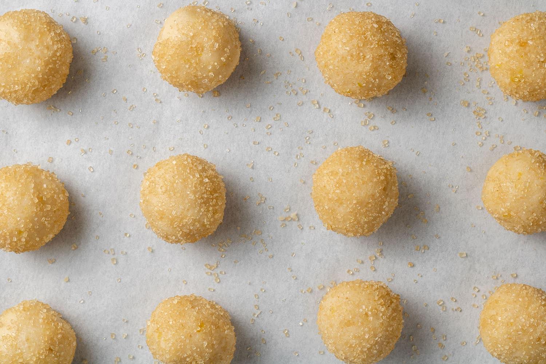 Unbaked lemon cookie dough balls on a parchment paper lined baking sheet.