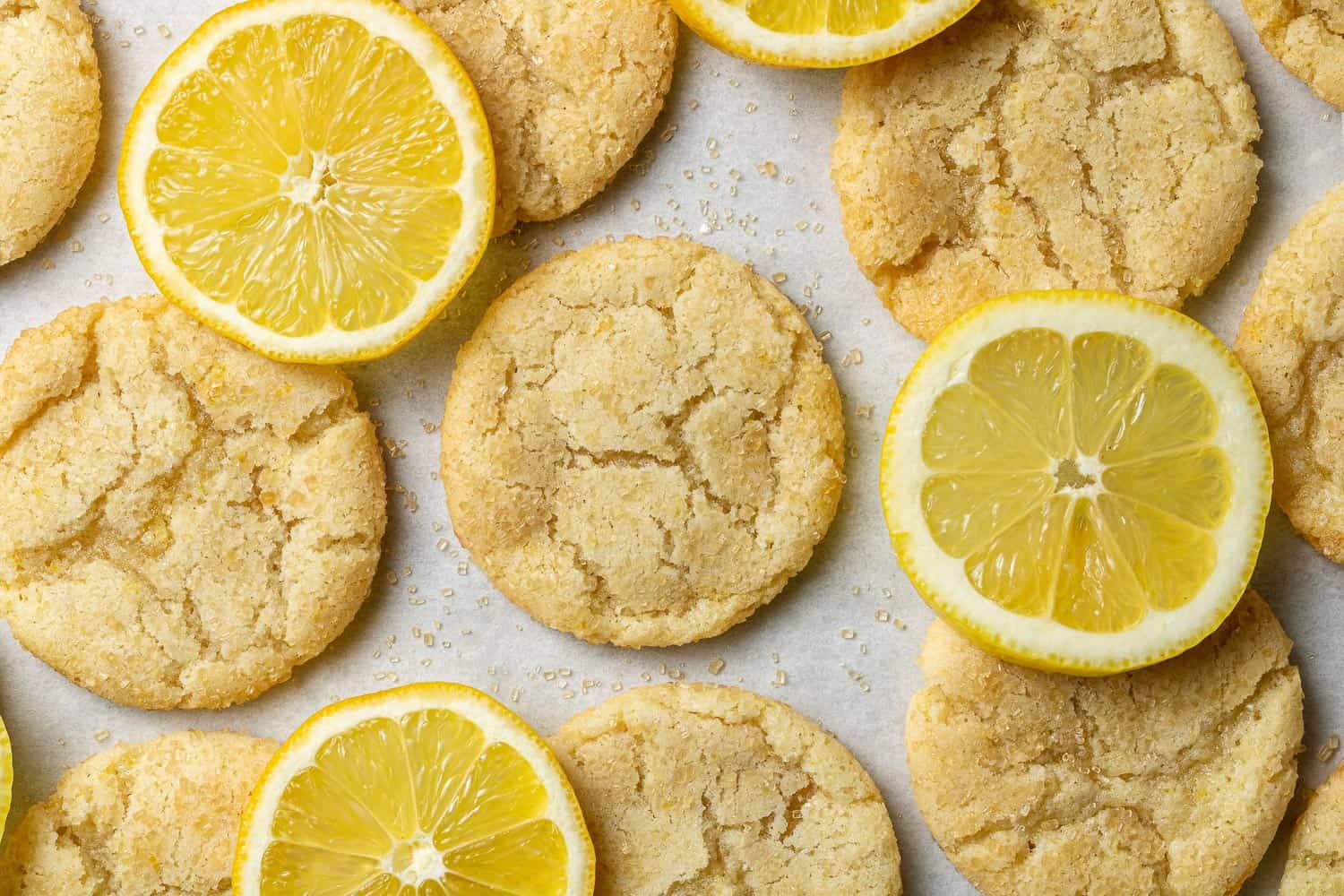 Close up of lemon sugar cookie with crinkled top, by lemon slices.