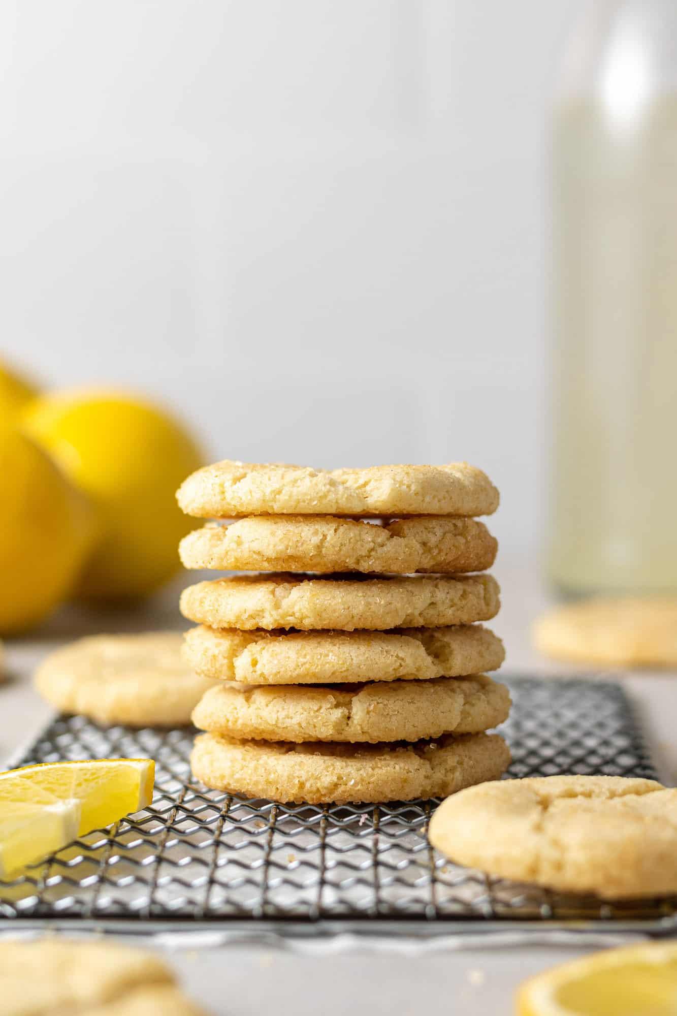 Lemon sugar cookies in a tall stack on wiring baking rack.