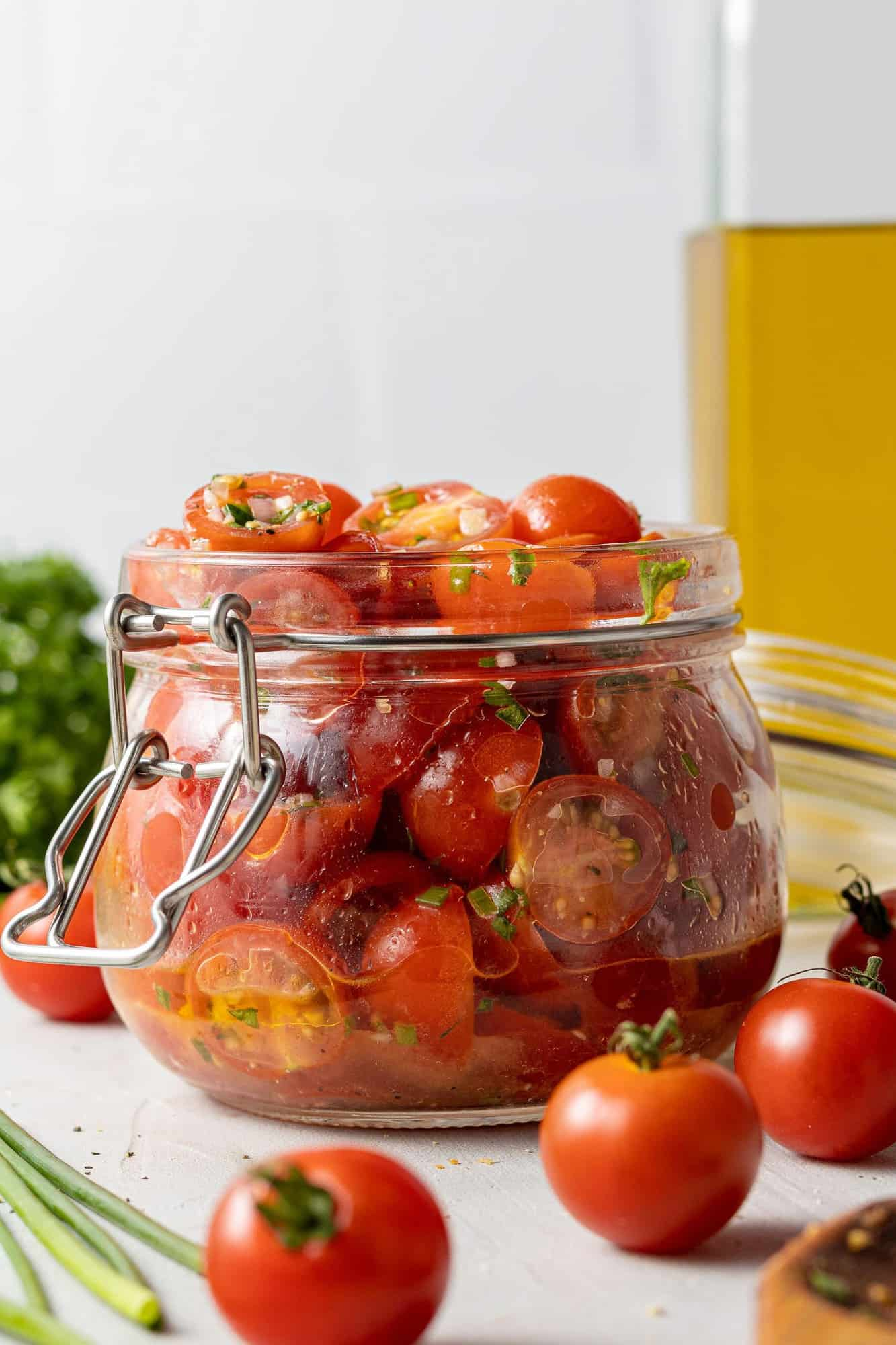 Tomatoes with olive oil and herbs in a small glass jar. Fresh tomatoes in the foreground.
