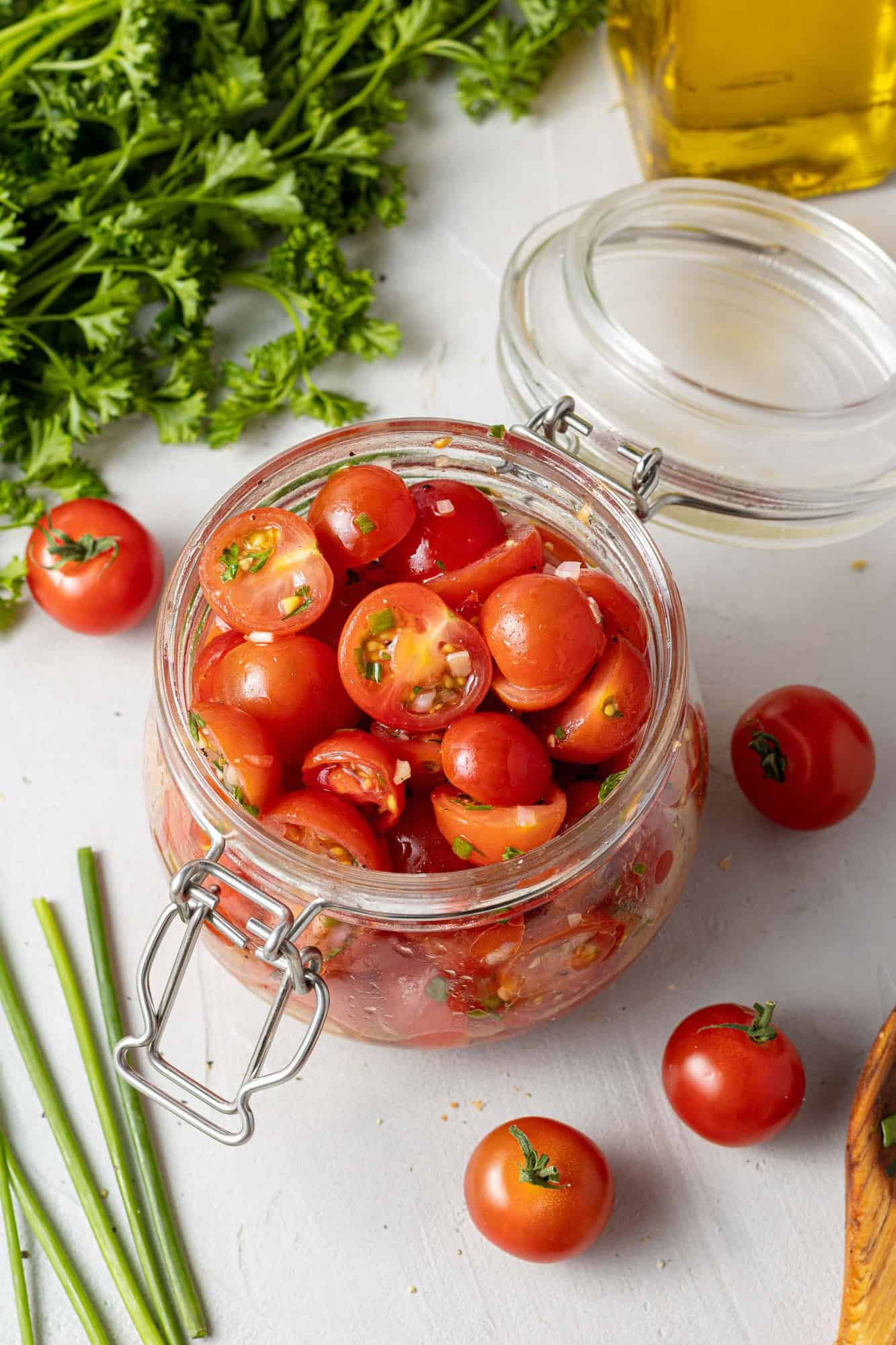 Tomatoes in a jar surrounded by fresh herbs.