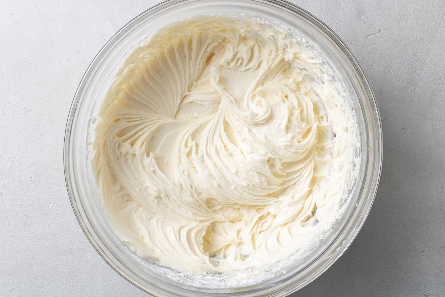 Cream cheese frosting in a clear glass mixing bowl.