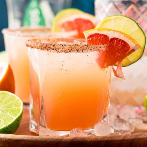 Peach colored paloma cocktail on ice with a grapefruit and lime wedge.