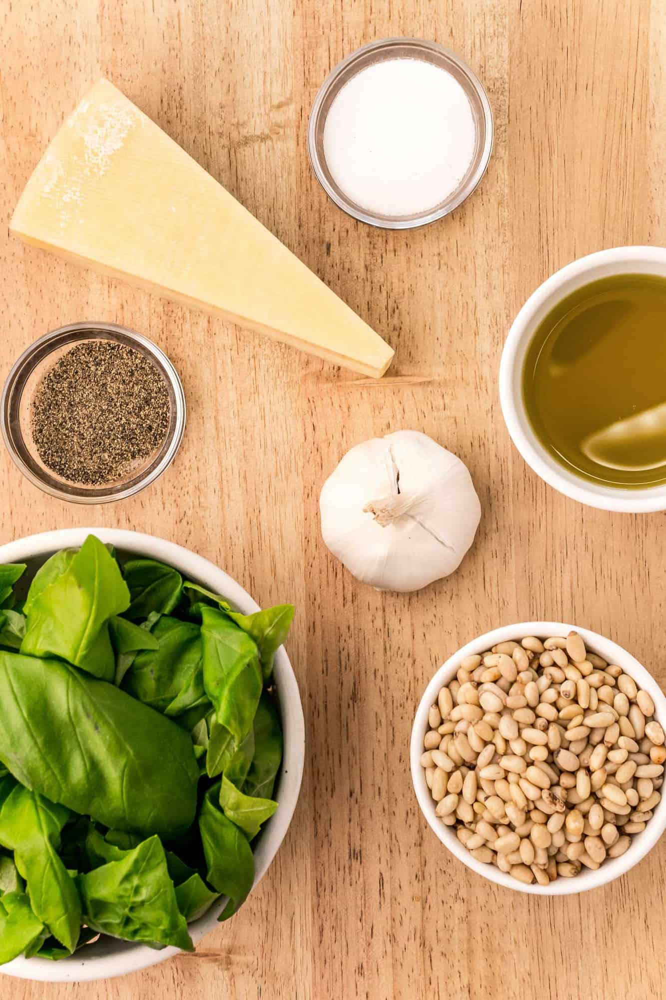 Overhead view of ingredients needed for recipe: basil, cheese, pine nuts, olive oil and garlic.