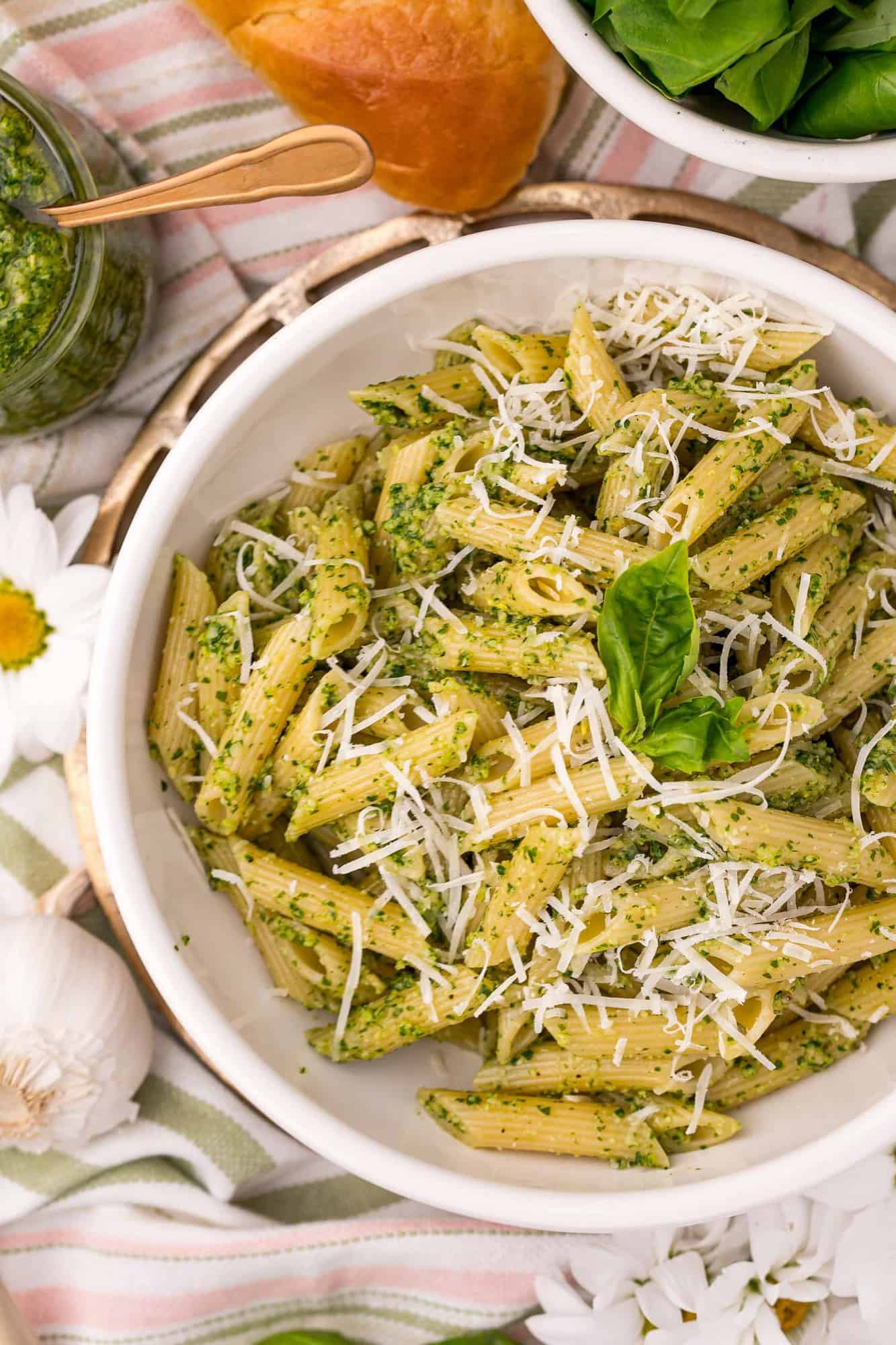 Overhead view of penne pasta in a white bowl, coated with pesto.