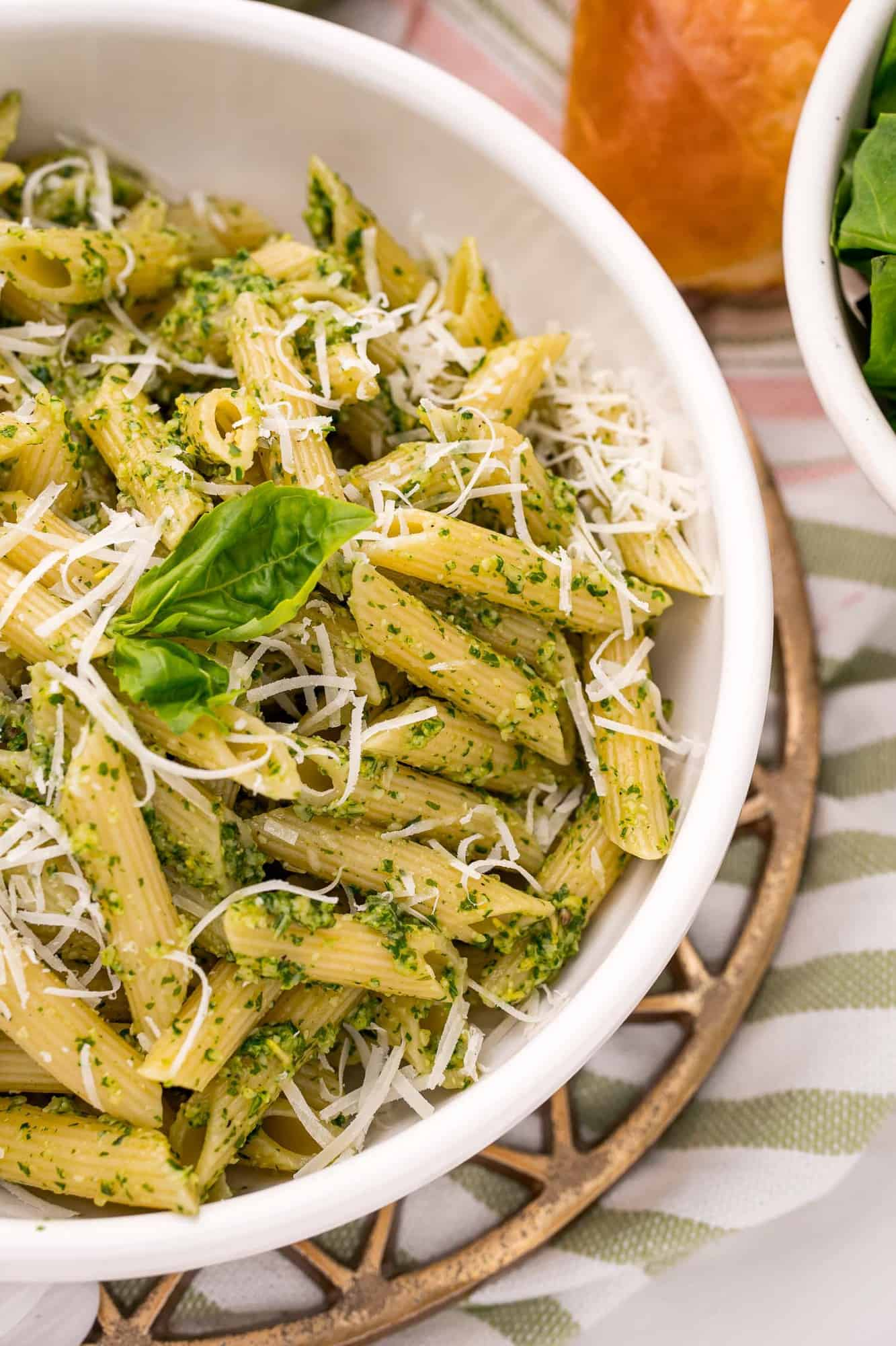 Penne pasta in a white bowl coated with pesto.