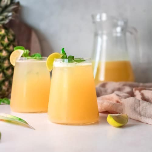 Light yellow drink with a pineapple in the background.