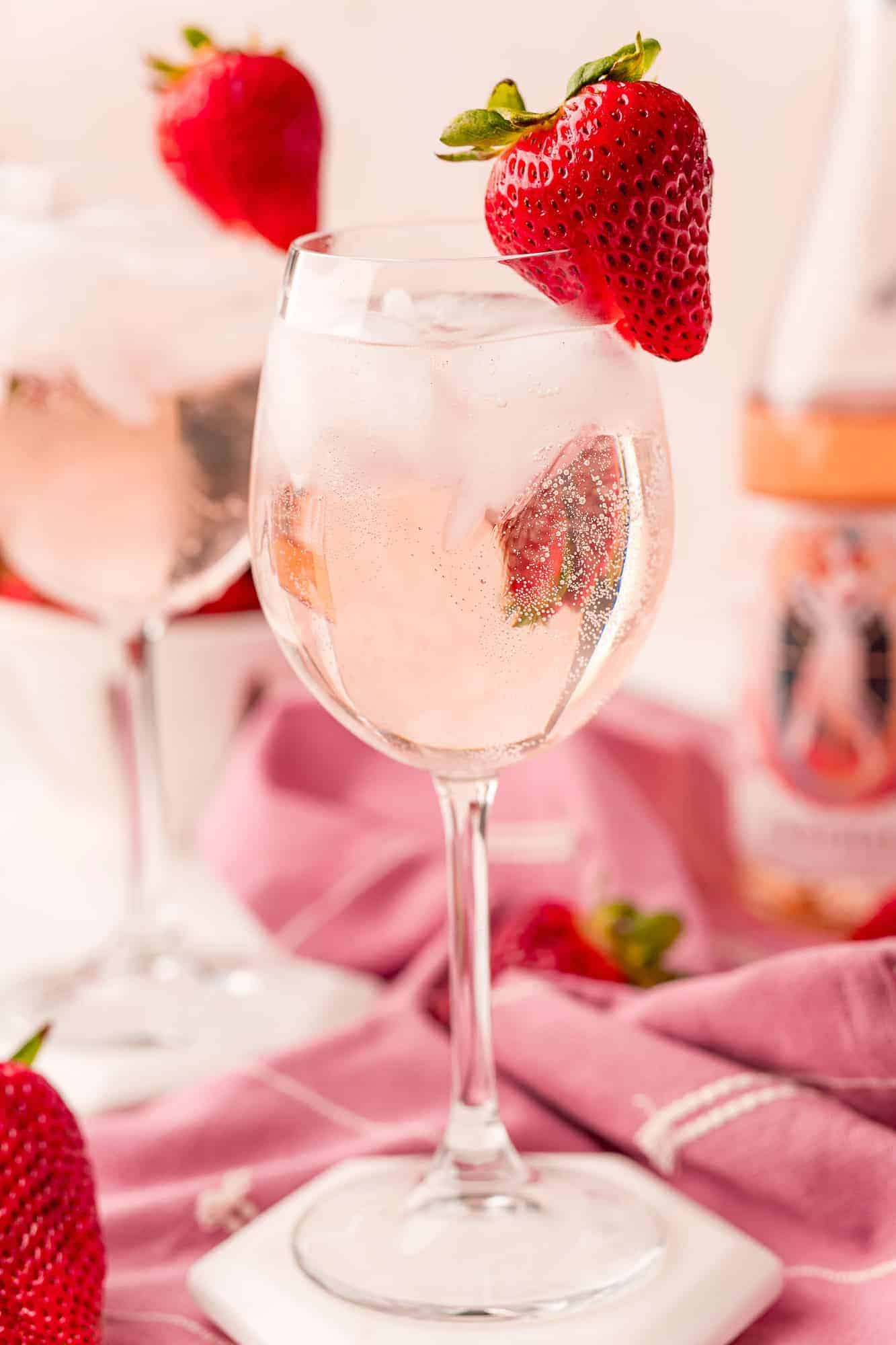 Close up of a wine glass with a rose spritzer, ice, and strawberry garnish.