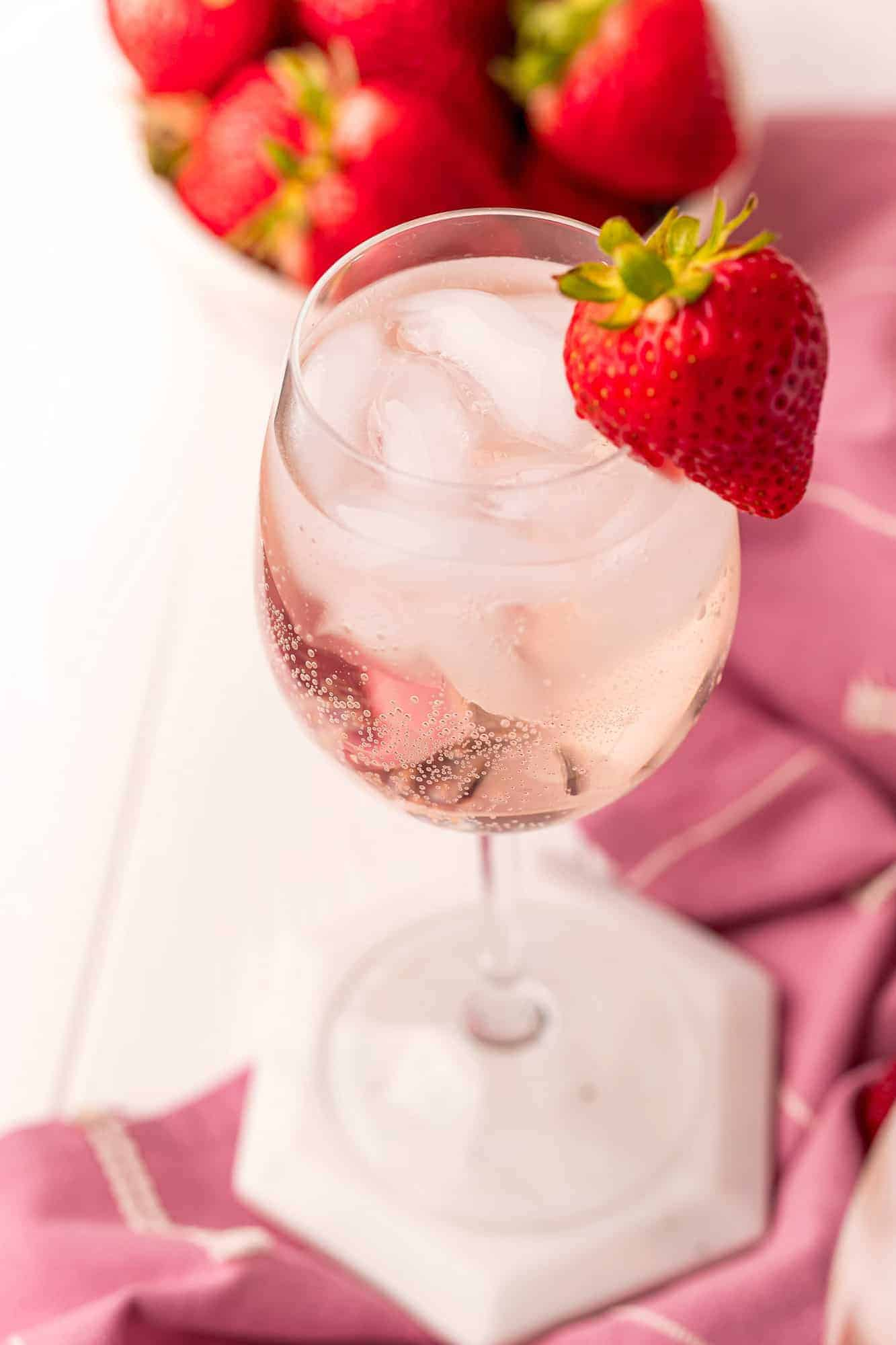 Light pink iced drink in a stemmed wine glass with a strawberry garnish.