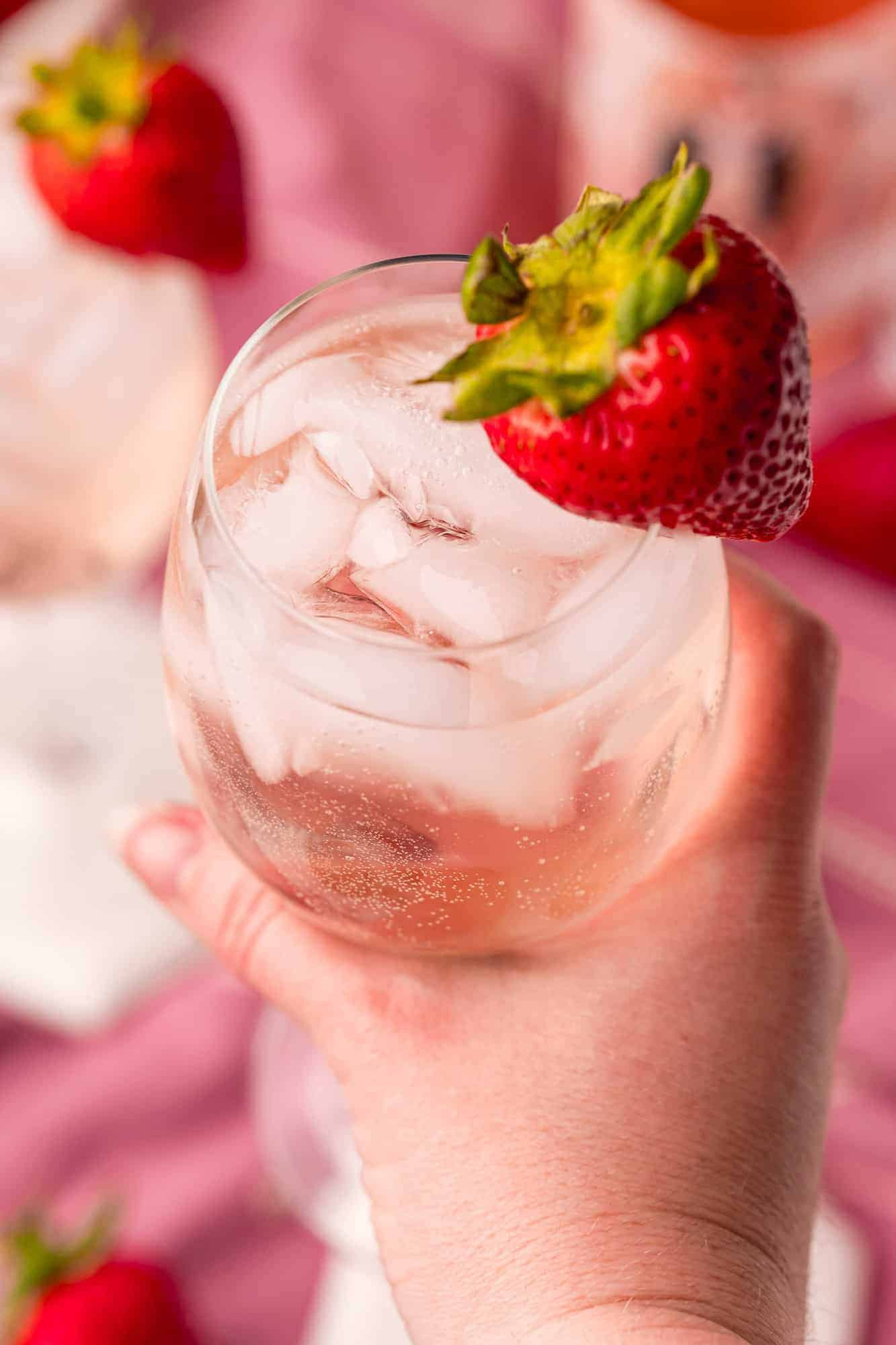 Iced cocktail with strawberry garnish in a person's hand.